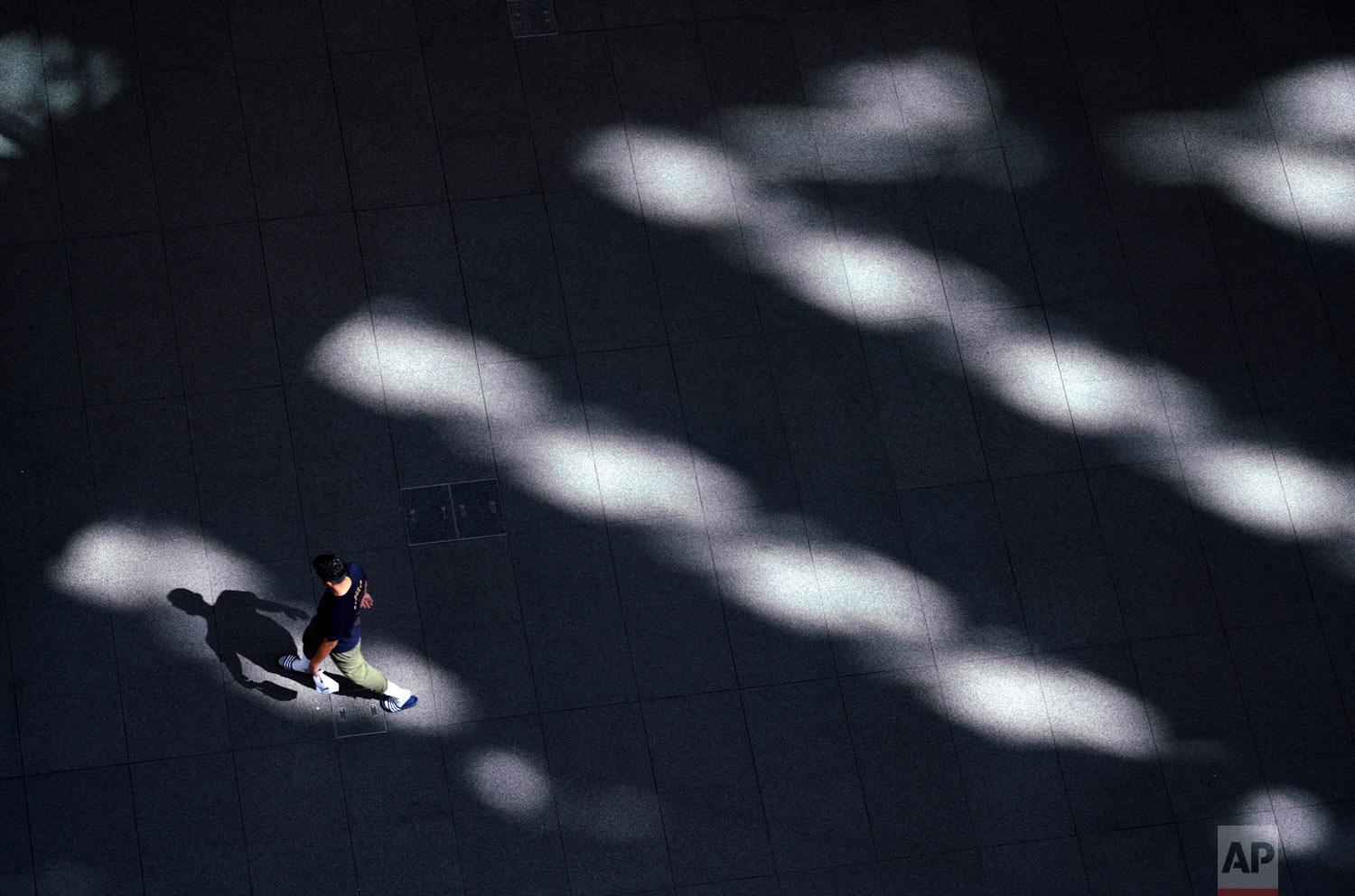 A man walks through a building in Tokyo as the temperature rose to 35 degrees Celsius (95 degrees Fahrenheit), Wednesday, Aug. 22, 2018. (AP Photo/Eugene Hoshiko)