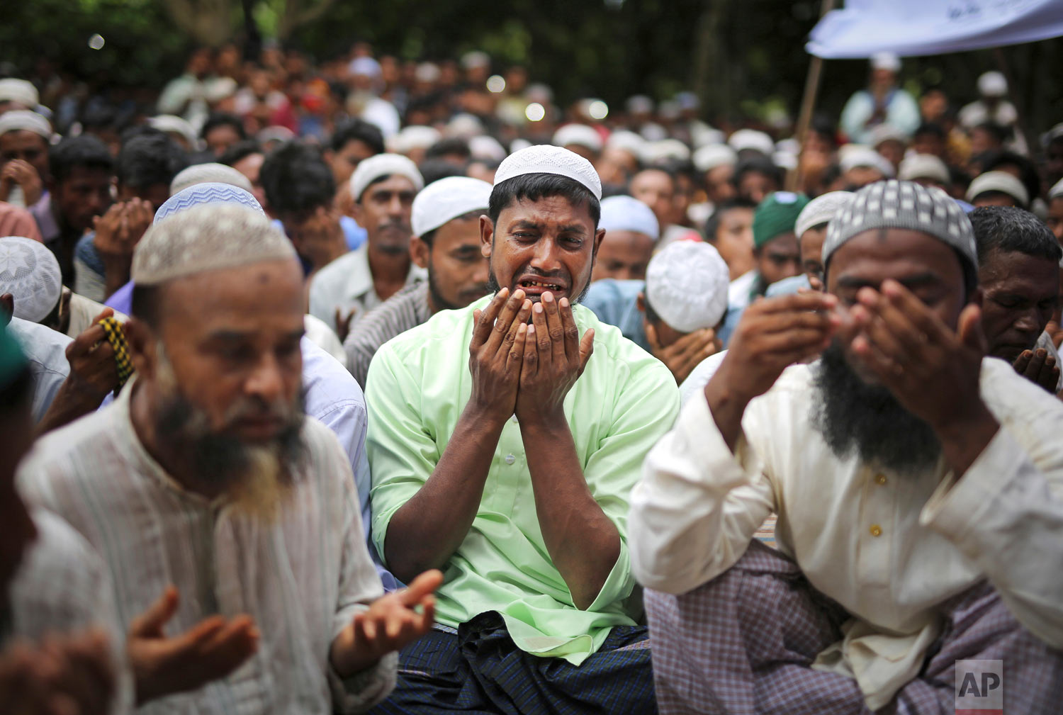 Rohingya refugees cry as they pray during a gathering to commemorate the first anniversary of Myanmar army's crackdown which led to a mass exodus of Rohingya Muslims to Bangladesh, at Kutupalong refugee camp in Bangladesh, Thursday, Aug. 25, 2018. (AP Photo/Altaf Qadri)