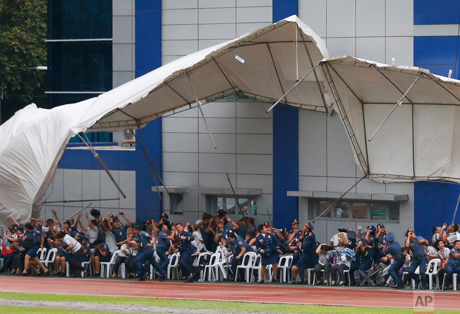 Philippine National Police officers and employees react as their tent is toppled by a hovering police helicopter performing a salute during the 117th Philippine National Police Service anniversary at Camp Crame in Quezon city, northeast of Manila, Philippines. Wednesday, Aug. 8, 2018. (AP Photo/Bullit Marquez)