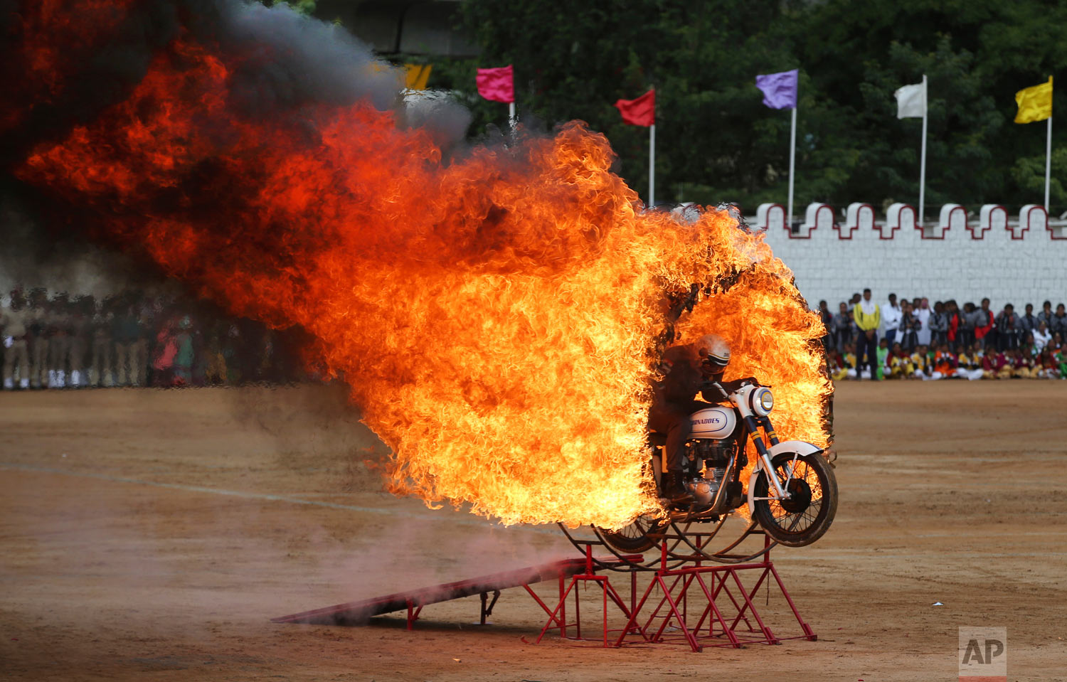 A member of ASC Tornados, the motorcycle display team of the Indian army, jumps through a fire ring as he performs a daredevil stunt during Indian Independence Day celebrations in Bangalore, India, Wednesday, Aug. 15, 2018. (AP Photo/Aijaz Rahi)