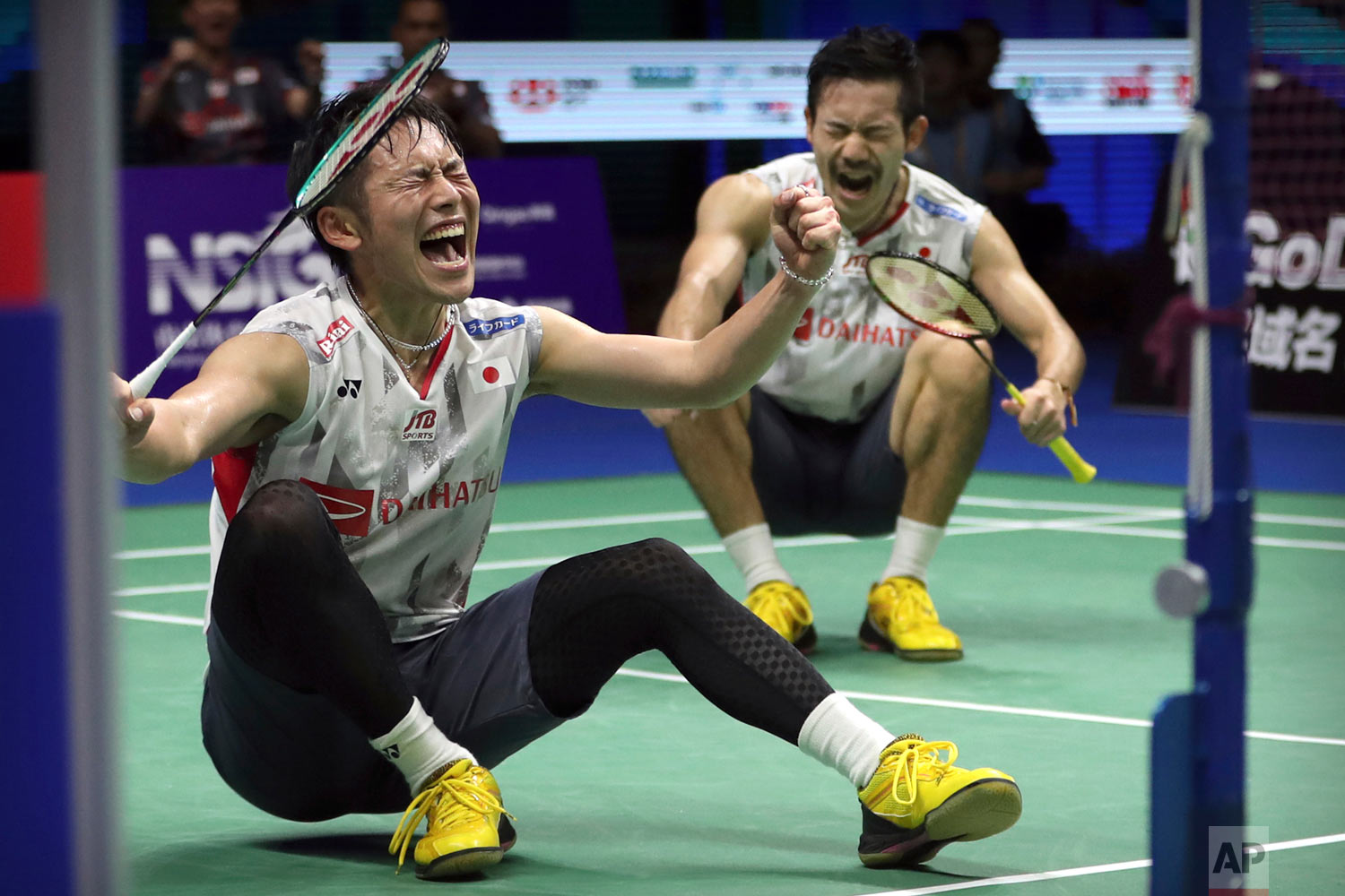 Takeshi Kamura, left, and Keigo Sonoda of Japan react after beating Marcus Fernaldi Gideon and Kevin Sanjaya Sukamuljo of Indonesia in their men's badminton doubles quarterfinal match at the BWF World Championships in Nanjing, China, Friday, Aug. 3, 2018. (AP Photo/Mark Schiefelbein)