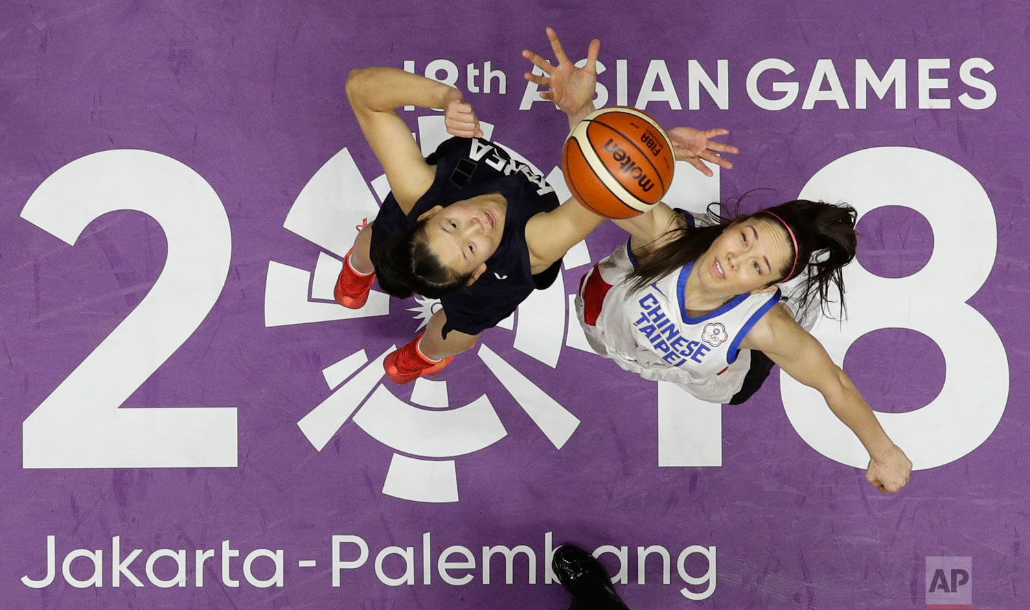 In this Friday, Aug. 17, 2018, photo, combined Koreas Ro Suk Yong, left, and Taiwan's Hsile Bao jump for ball possession during their women's basketball match at the 18th Asian Games in Jakarta, Indonesia. (AP Photo/Aaron Favila)