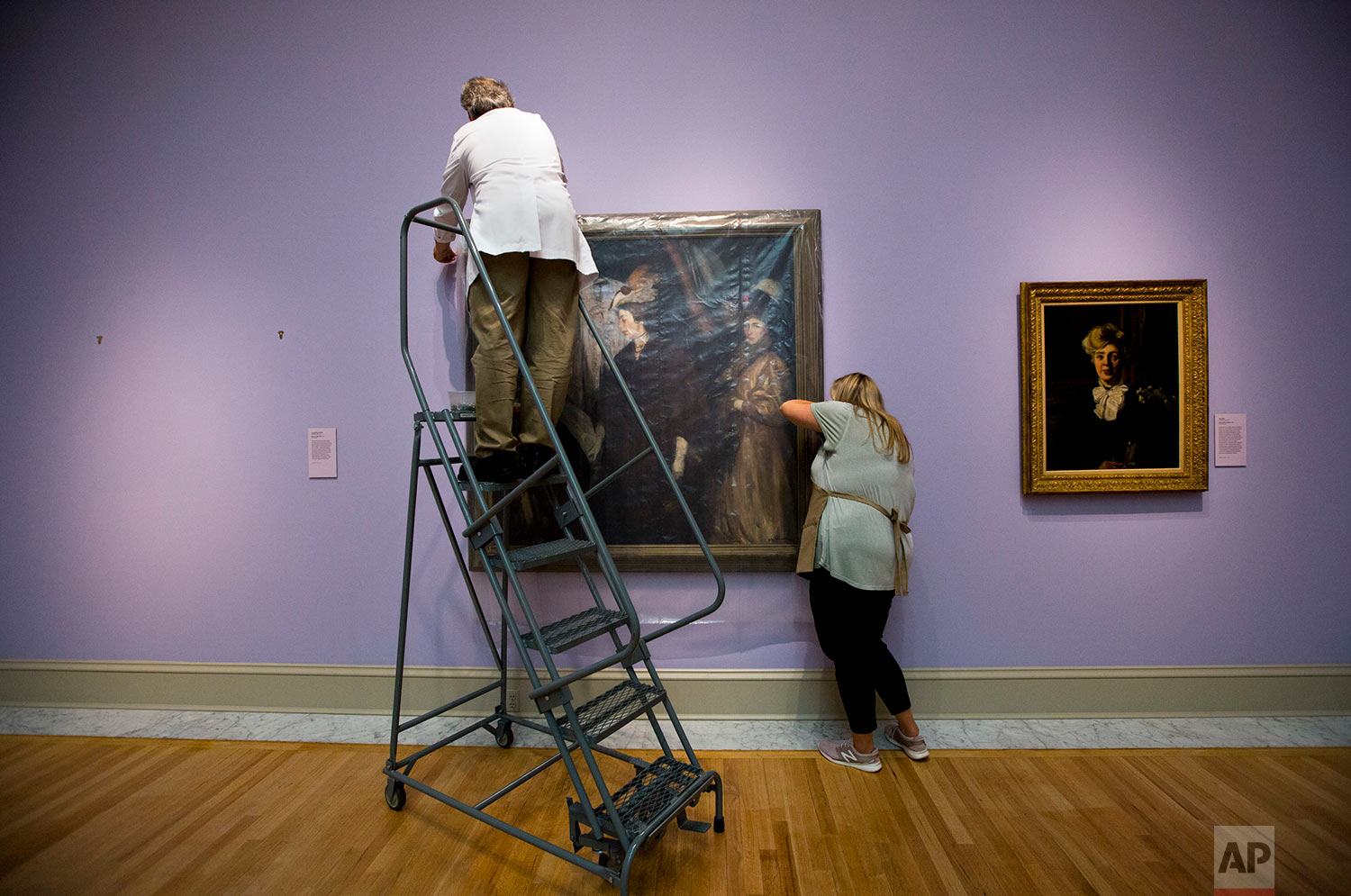 """Mark Lewis, left, conservator, and Alisa Reynolds, associate registrar, secure the painting """"The Shoppers"""" by William James Glackens at the Chrysler Museum of Art on Tuesday, Sept. 11, 2018 in Norfolk, Va. As category 4 Hurricane Florence approaches, staff members pull priceless paintings off the walls near windows and skylights on. Later on, the entrance to the museum will be sandbagged. (The' N. Pham/The Virginian-Pilot via AP)"""