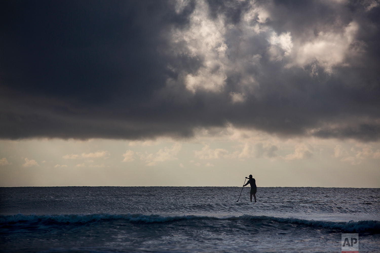 """A paddle boarder gets in some exercise in the early morning off the beach at the Isle of Palms, S.C., as Hurricane Florence spins out in the Atlantic ocean Wednesday, Sept. 12, 2018.  The National Weather Service says Hurricane Florence """"will likely be the storm of a lifetime for portions of the Carolina coast."""" (AP Photo/Mic Smith)"""