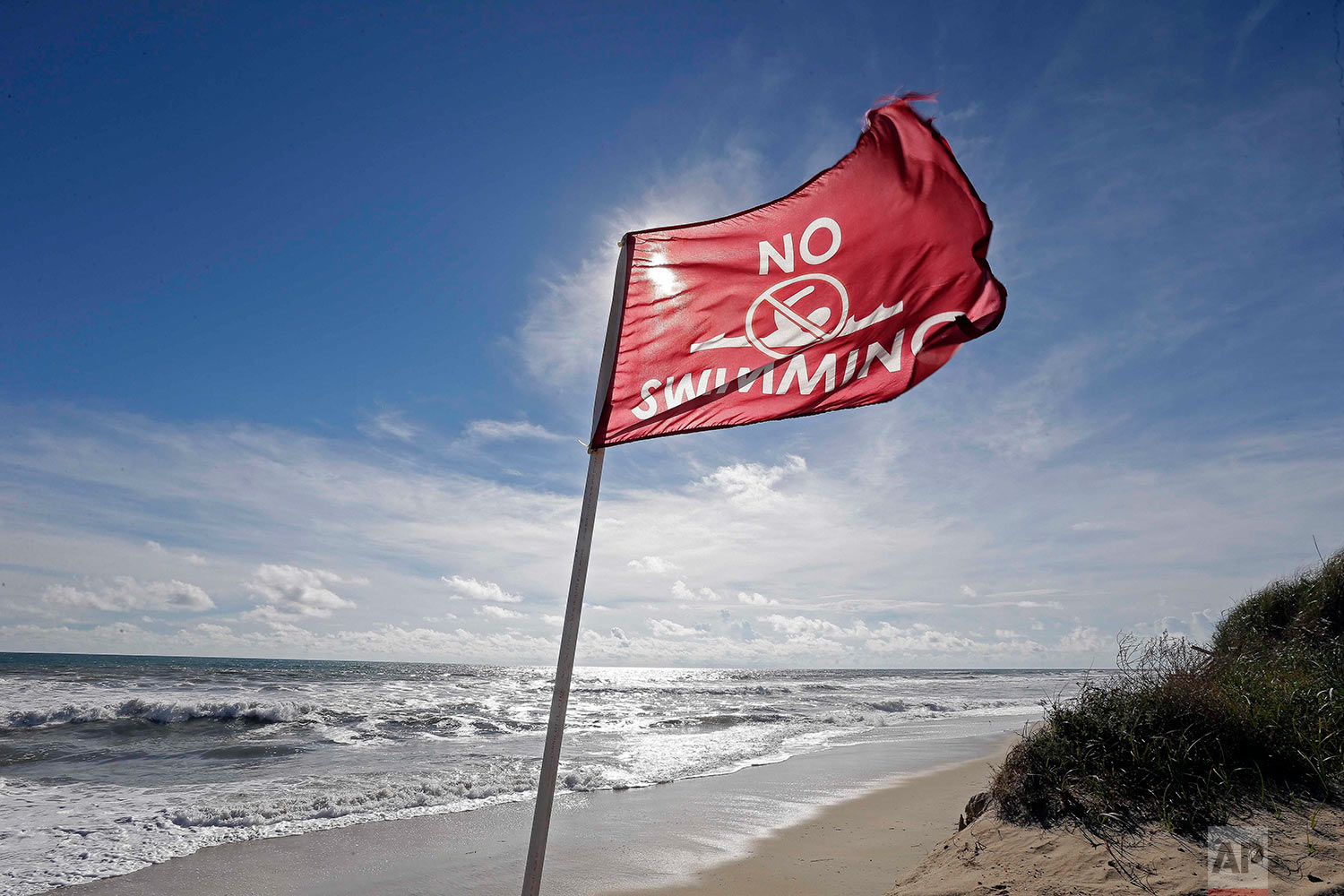 """A warning flag flies in the gusty wind near Nags Head, N.C., Wednesday, Sept. 12, 2018 as Hurricane Florence approaches the coast of the Carolinas. The National Weather Service says Florence """"will likely be the storm of a lifetime for portions of the Carolina coast.""""(AP Photo/Gerry Broome)"""