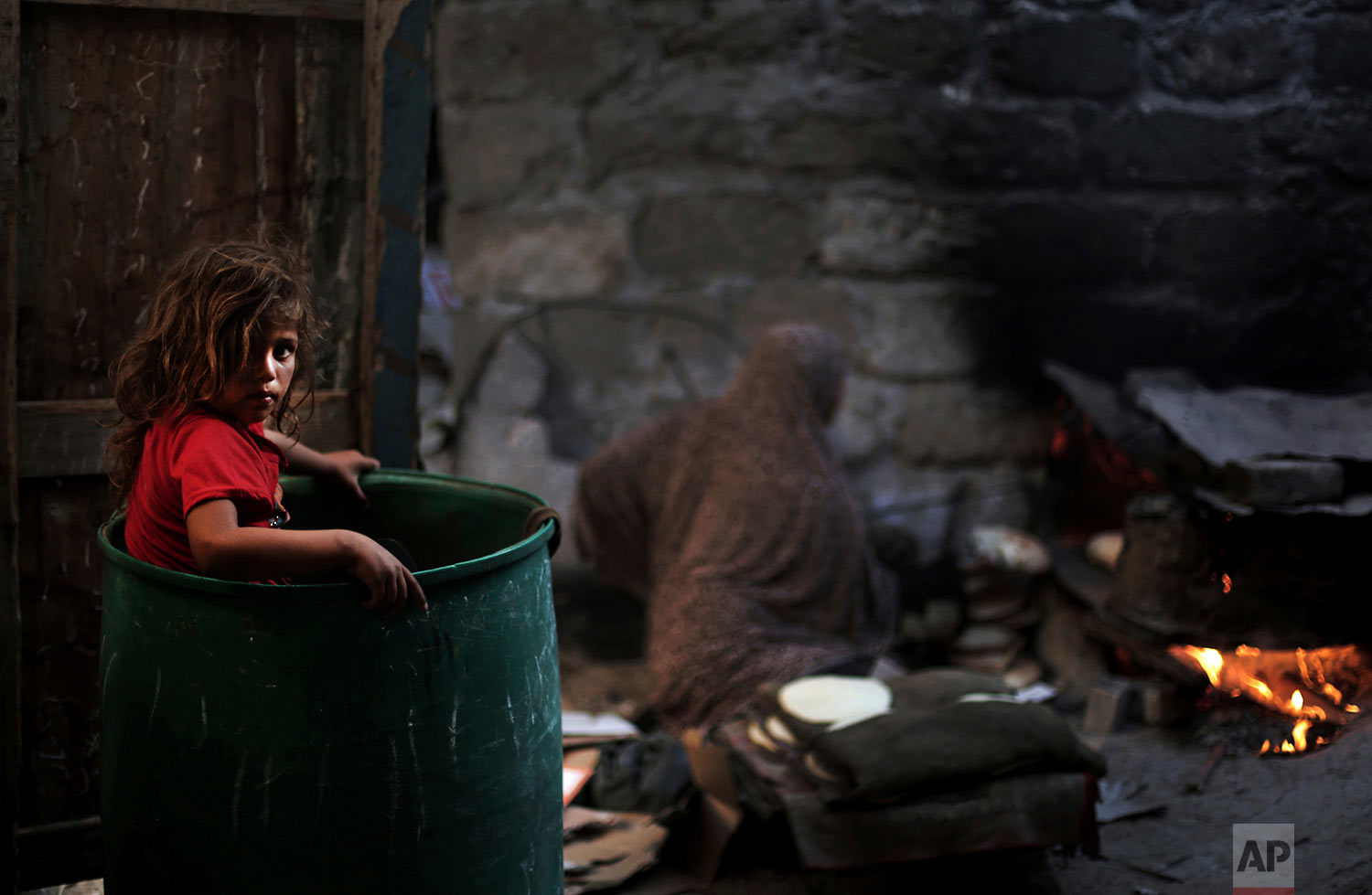 In this June 20, 2016 photo, a Palestinian girl plays in a barrel as her mother bakes bread for a Ramadan dinner at their house in el-Zohor slum, on the outskirts of Khan Younis refugee camp, southern Gaza Strip. (AP Photo/Khalil Hamra)