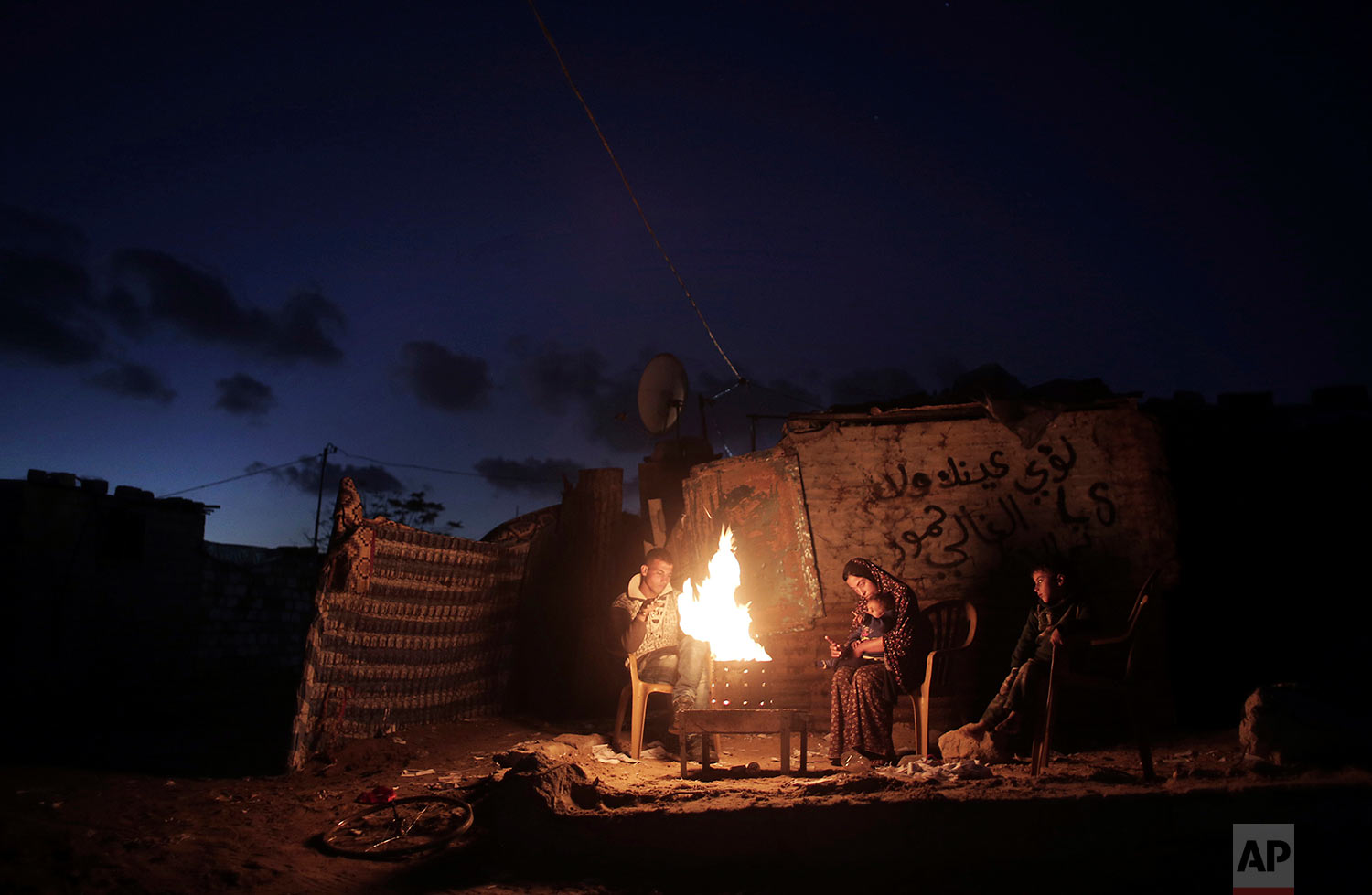 In this Jan. 15, 2017 photo, a Palestinian family warm themselves with a fire outside their makeshift house during a power cut in a poor neighborhood in Khan Younis, the southern Gaza Strip. (AP Photo/Khalil Hamra)