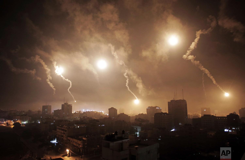 In this July 29, 2014 photo, Israeli forces' flares light up the night sky of Gaza City. (AP Photo/Khalil Hamra)