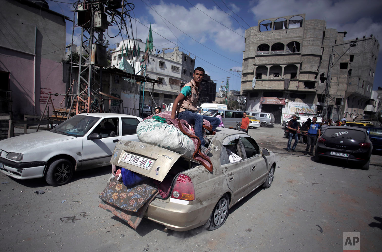 In this July 26, 2014 photo, Palestinians salvage what little of their belongings they could from their homes during a 12-hour cease-fire in Gaza City's Shijaiyah neighborhood. (AP Photo/Khalil Hamra)