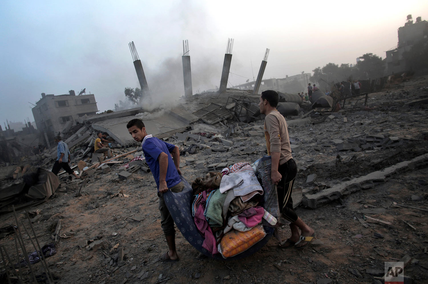 In this July 8, 2014 photo, Palestinians try to salvage what they can of their belongings from the rubble of a house destroyed by an overnight Israeli airstrike in Gaza City. (AP Photo/Khalil Hamra)