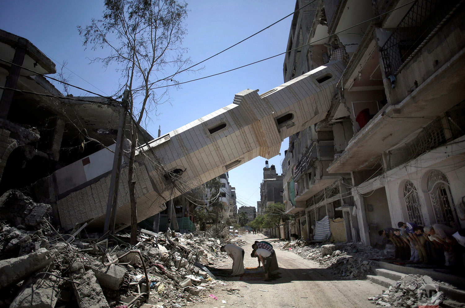 In this Aug. 8, 2014 photo, Palestinians pray beneath the fallen minaret of the Soussi mosque that was hit by Israeli strikes in Gaza City. (AP Photo/Khalil Hamra)