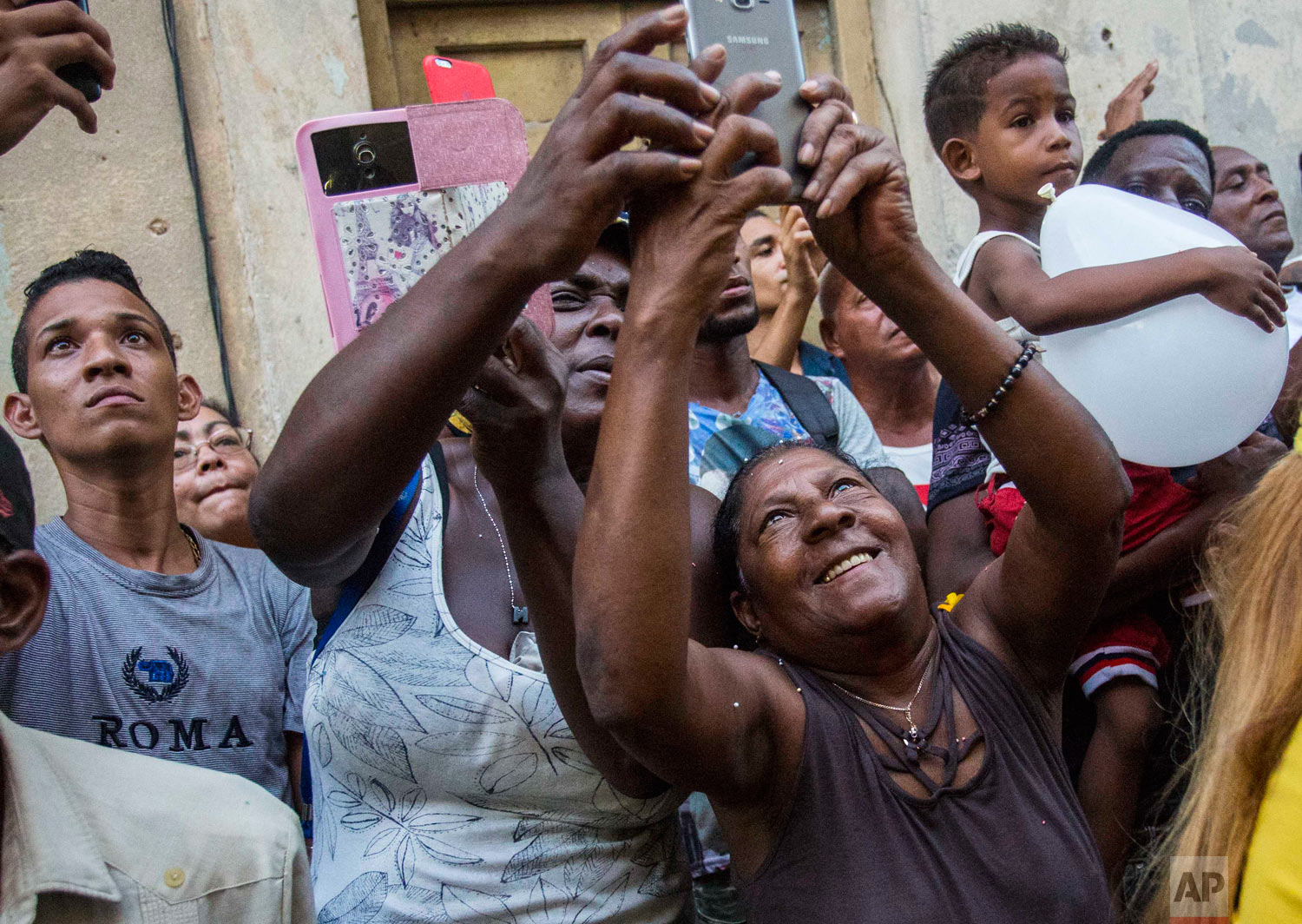 """People use their phones to take pictures of the annual Virgin of Charity procession in Havana, Cuba, late Saturday, Sept. 8, 2018. Cuba's patron saint is also recognized as a powerful deity in the African-influenced religion of Santeria, which refers to her as """"Ochun."""" (AP Photo/Desmond Boylan)"""