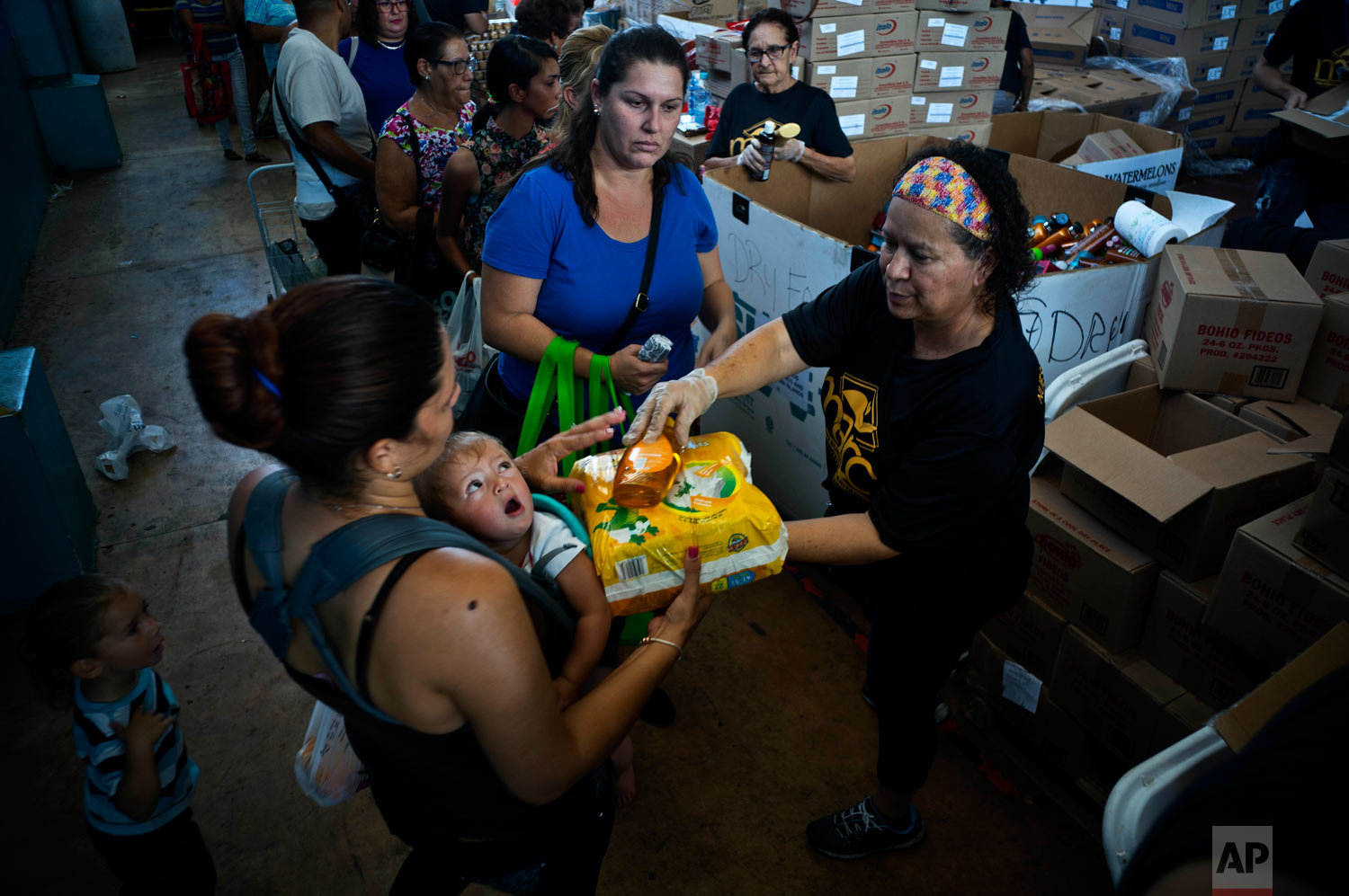 A woman receives free diapers and shower gel from the charity MARC Ministry. Sept. 7, 2018. (AP Photo/Ramon Espinosa)
