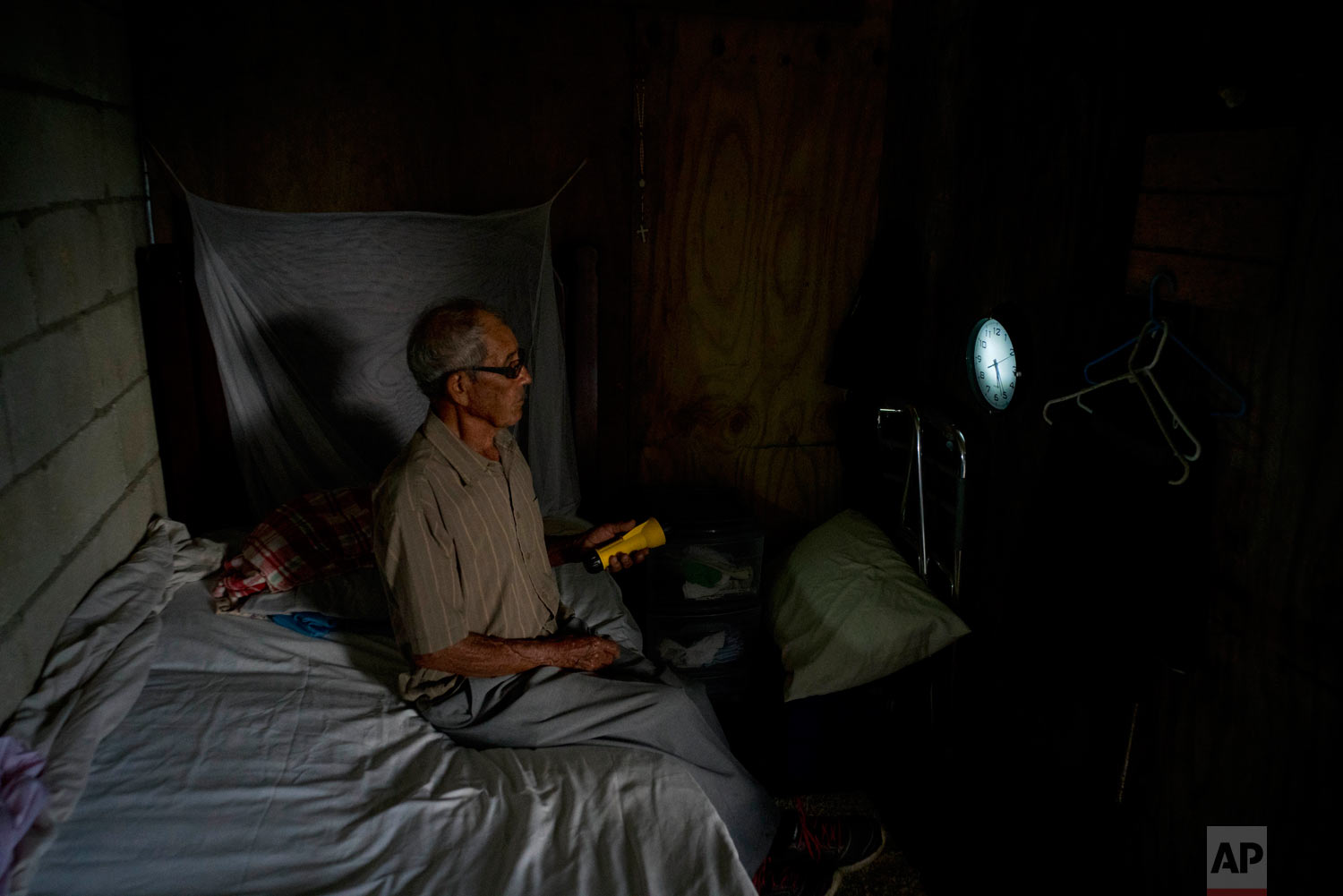 Ramon Alicea Burgos uses a flashlight to read the time on the clock on the wall of a temporary wooden room he built under the structure of his partially re-built home. Sept. 8, 2018. (AP Photo/Ramon Espinosa)