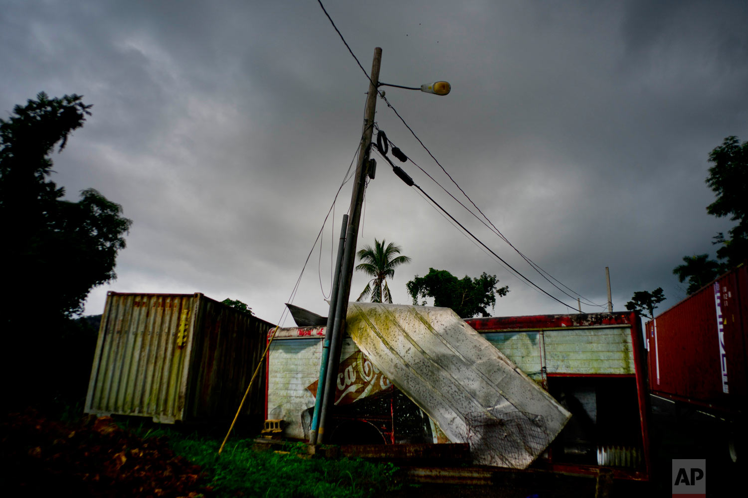 In this Sept. 7, 2018 photo, a Coca-Cola trailer destroyed one year ago by Hurricane Maria stands on the side of the road in Orocovis, Puerto Rico. (AP Photo/Ramon Espinosa)