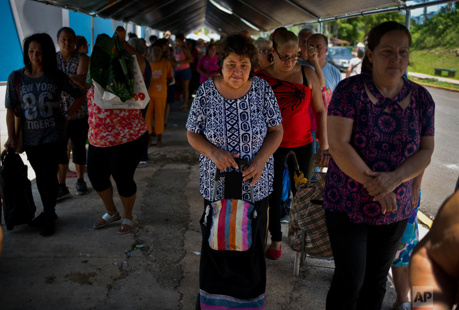 In this Sept. 7, 2018 photo, Elia de Jesus Acebedo waits in a line for donated food and other staples from the MARC Ministry, a non-profit charity in Manati, Puerto Rico. Acebedo, 67, said she and her sister rented a home that was destroyed by Hurricane Maria one year go, leaving them with nothing. (AP Photo/Ramon Espinosa)
