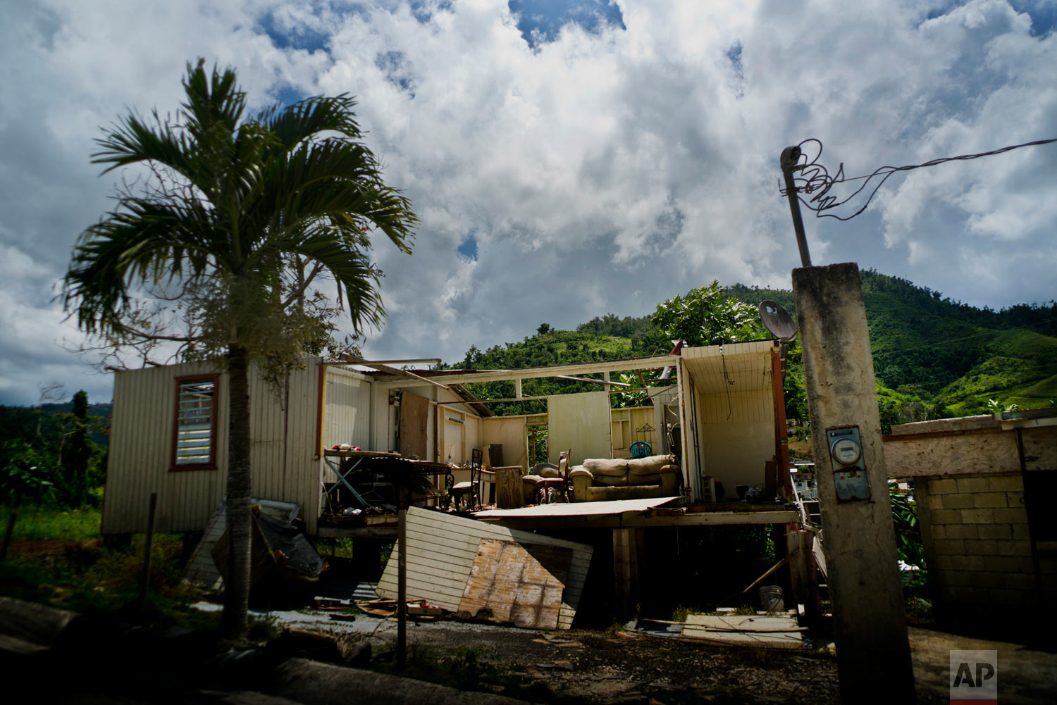In this Sept. 8, 2018 photo, a home abandoned after Hurricane Maria hit one year ago stands full of furniture in the San Lorenzo neighborhood of Morovis, Puerto Rico. (AP Photo/Ramon Espinosa)