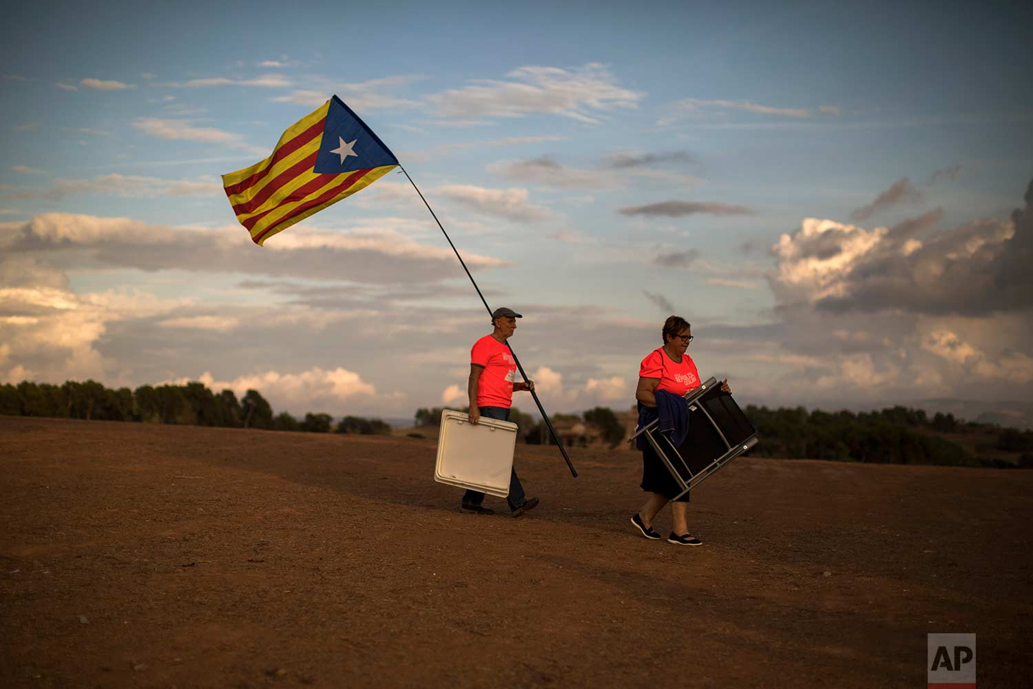 In this Tuesday, Sept. 18, 2018 photo, pro independence people carry chairs and a picnic basket, as they arrive to a field overlooking the Lledoners prison in Sant Joan de Vilatorrada, about 50 kilometres away from Barcelona, Spain. (AP Photo/Emilio Morenatti)