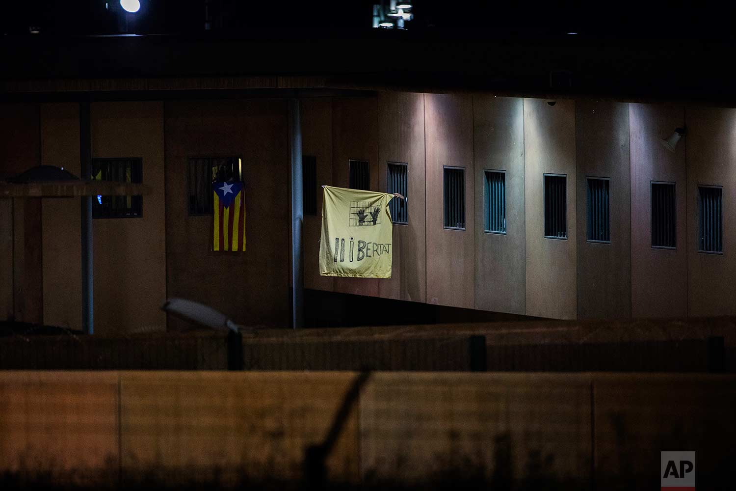 "In this Tuesday, Sept. 18, 2018 photo, an ""estelada"" or independence flag, and a banner reading in Catalan ""Freedom"", are waved from windows of cells in Lledoners prison, in Sant Joan de Vilatorrada, about 50 kilometres away from Barcelona, Spain. (AP Photo/Emilio Morenatti)"