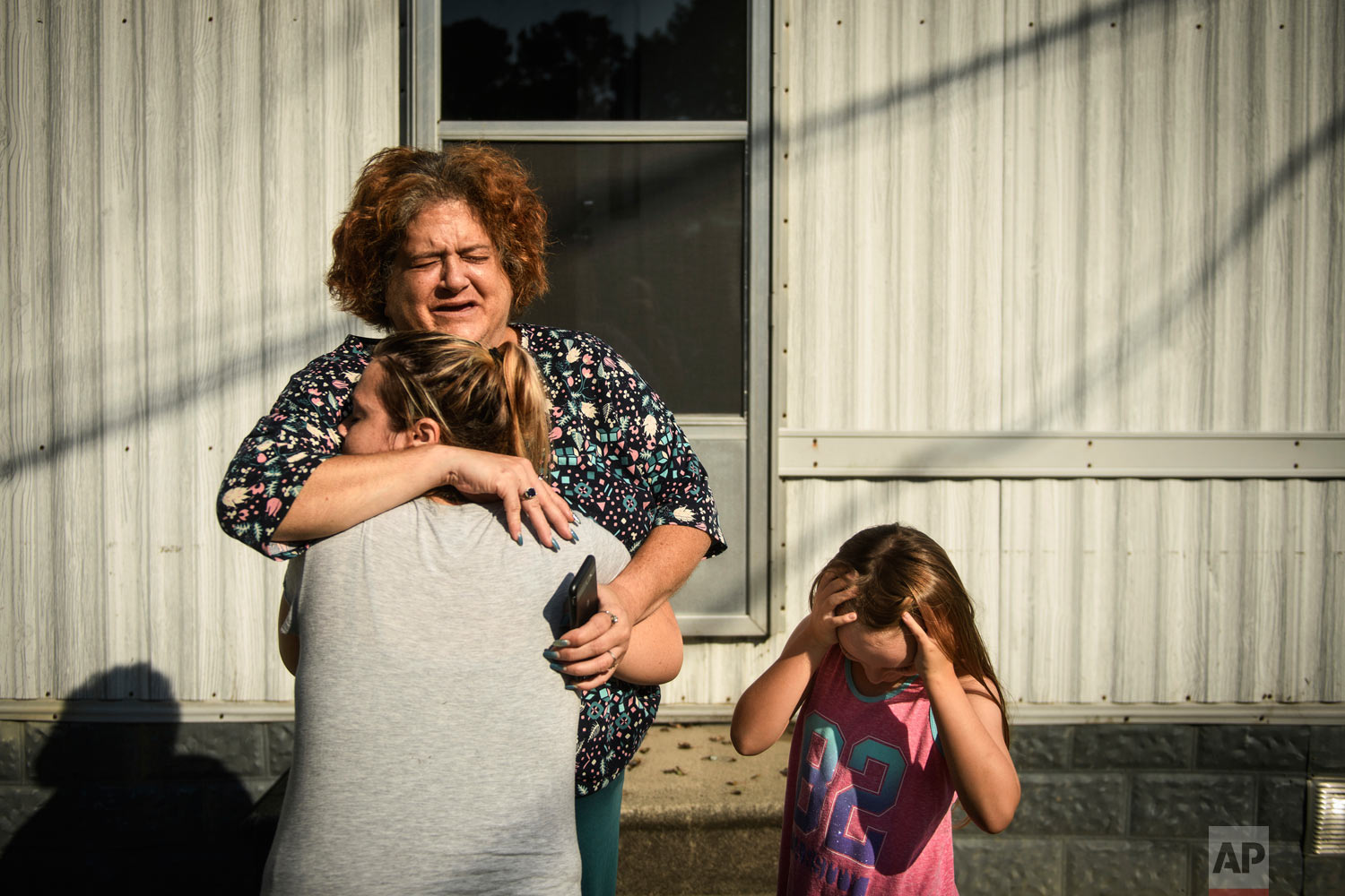 Melanie Wensel gives her neighbor Linda Remmel a hug as Wensel's daughter, Emily, stands near, Thursday, Sept. 20, 2018, at Speranza Mobile Home Park off of Manchester Road in Spring Lake, N.C. Most of the residents of the park had their homes flooded from Hurricane Florence and will have to find a new place to live. (Andrew Craft/The Fayetteville Observer via AP)
