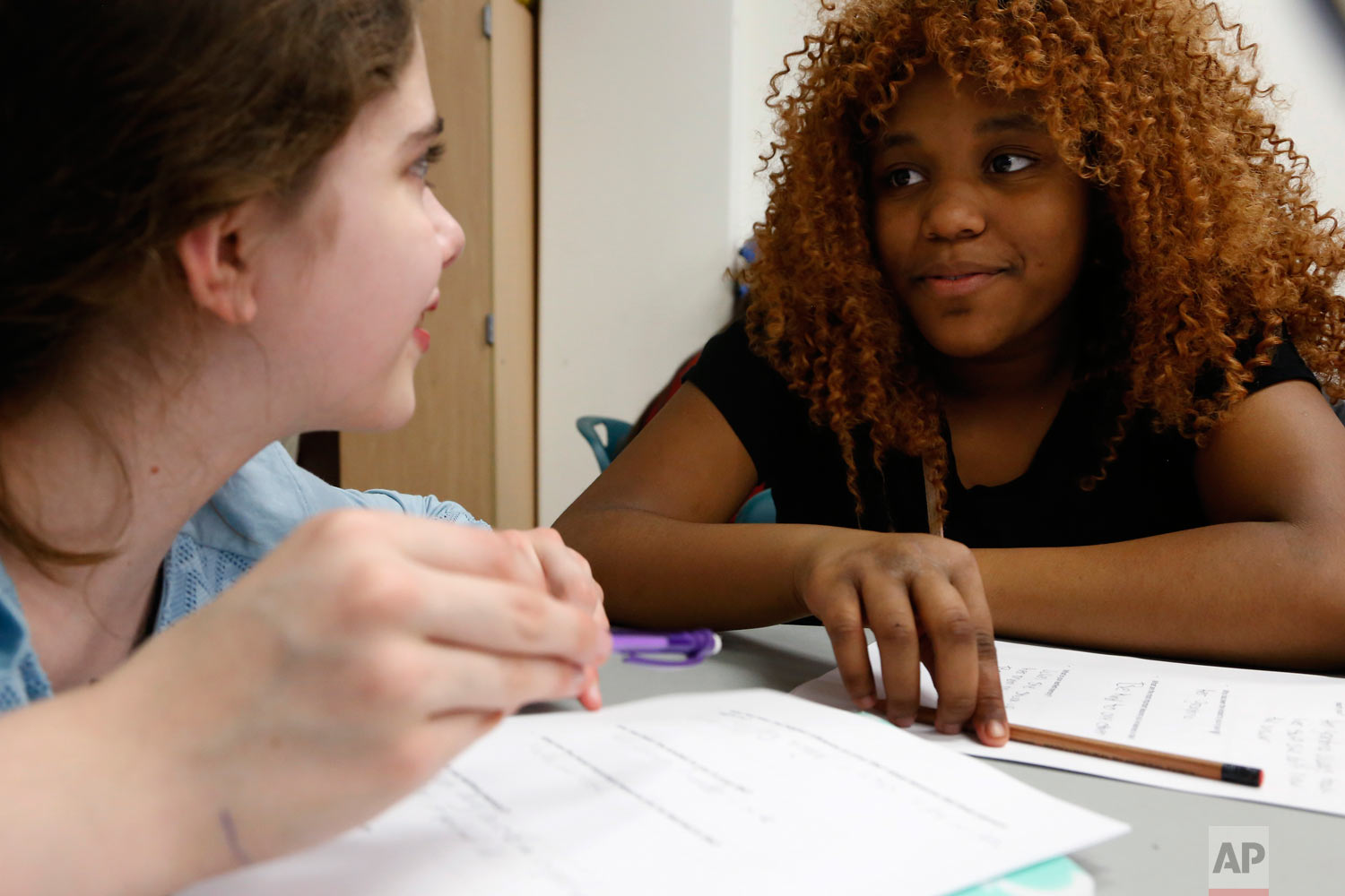 In this April 27, 2017, photo, Miracle Shanklin, right, and Isabella Iniguez, both age 12 when this photo was taken, talk during an ice-breaker exercise in Chicago. The session brought together students from the public Manierre Elementary School and the private Catherine Cook School - on opposite sides of Sedgwick Street. (AP Photo/Martha Irvine)