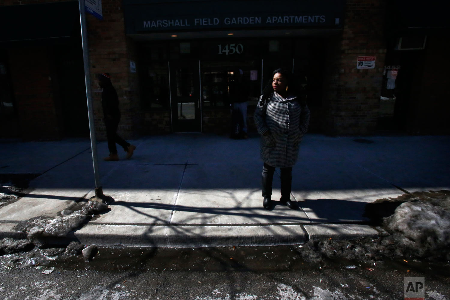 In this March 5, 2015, photo, Precious Murphy stands outside Marshall Field Garden Apartments, one of the last larger-scale buildings with subsidized housing in a neighborhood that was once home to Chicago's Cabrini-Green housing project, in Chicago. Despite her interest in Art on Sedgwick and friendship with its founder, Charlie Branda, Murphy and her four children moved to Bloomington, Indiana, to start a new life. (AP Photo/Martha Irvine)