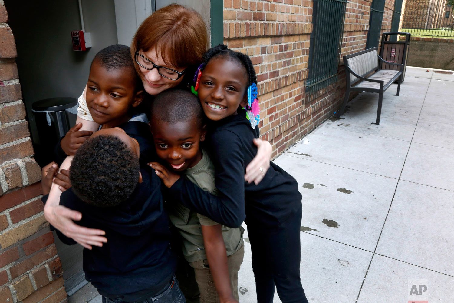 """In this June 25, 2018, photo, Charlie Branda, founder of Art on Sedgwick, hugs a few young residents of Marshall Field Garden Apartments in Chicago. Branda, whom many children call """"art teacher,"""" is a former commercial banker who left the profession to raise her two children, now teens. Though she doesn't consider herself an artist, she later opened a neighborhood art studio called Art on Sedgwick to try to unite a neighborhood divided by income and race. (AP Photo/Martha Irvine)"""