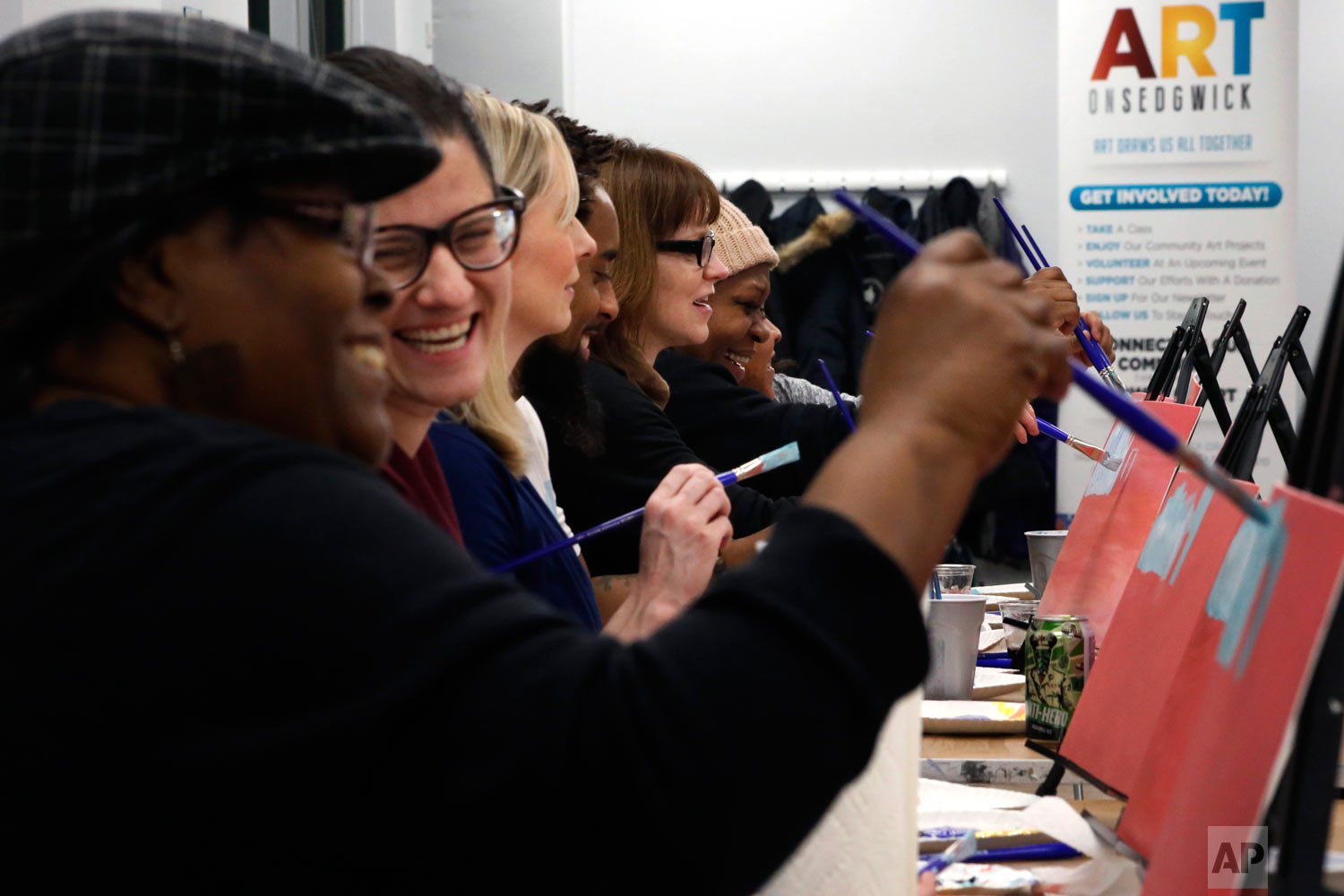 """In this Feb. 10, 2018, photo, Adell Thomas, left, cracks a joke during a """"Sip and Paint"""" class for adults at Art on Sedgwick, in Chicago. The class brings people from different backgrounds together to socialize. Art on Sedgwick was founded by Charlie Branda, center in glasses, as a way to unify a neighborhood that is divided by income and race. The core group of regulars is one of the studio's successes. """"But we're nowhere near where I want us to be,"""" says Thomas, who has become a board member at Art on Sedgwick. (AP Photo/Martha Irvine)"""