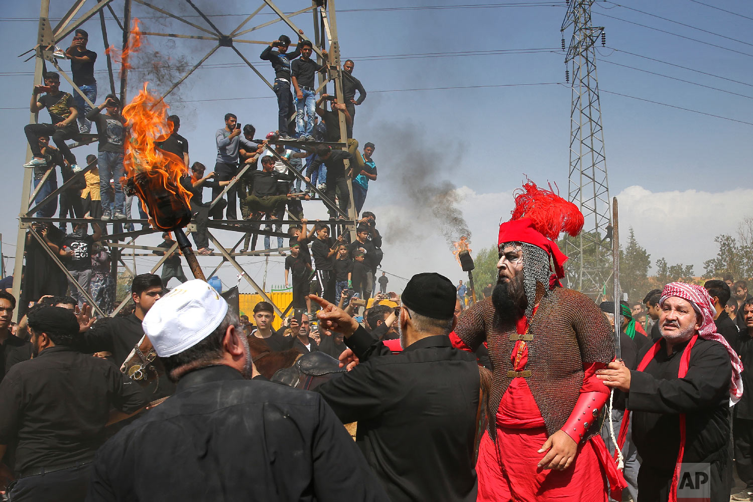 Shiites in costumes re-enact events of Ashoura while Iranian and Iraqi Shiite Muslims mourn in a procession, in southern Tehran, Iran, Sept 20, 2018. (AP Photo/Ebrahim Noroozi)