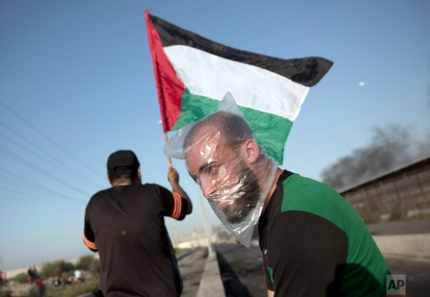 A Palestinian protester wears a plastic bag on his head as a protection from teargas as another waves a national flag during a protest at the entrance of Erez border crossing between Gaza and Israel, in the northern Gaza Strip, Sept. 26, 2018. (AP Photo/Khalil Hamra)