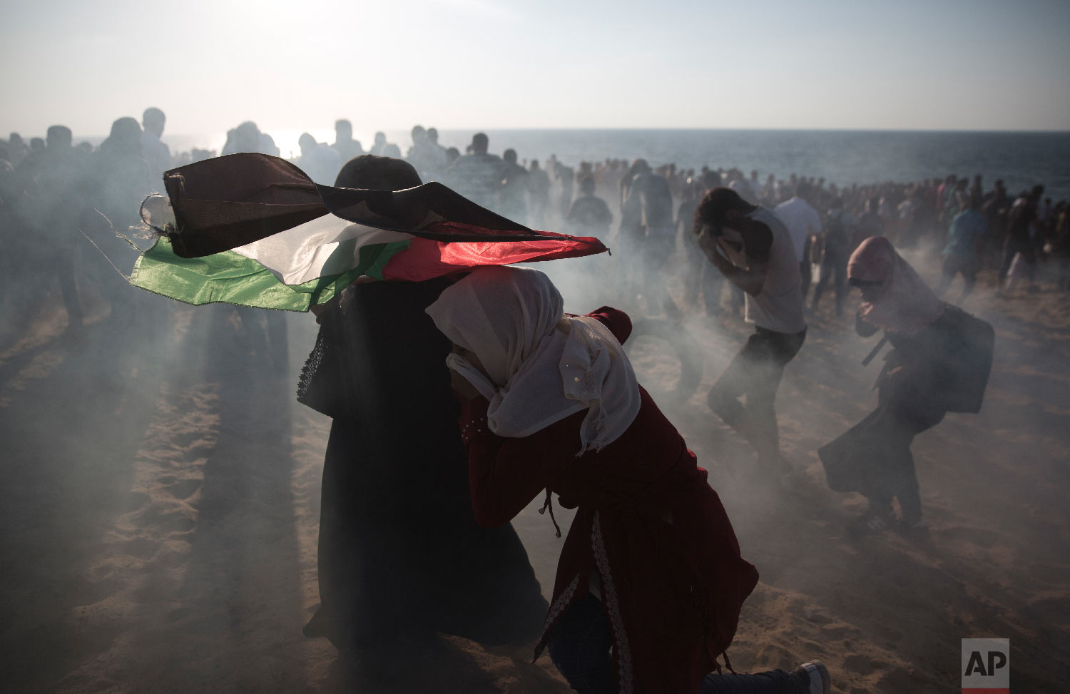 Palestinian protesters run for cover from teargas fired by Israeli soldiers during a protest on the beach at the border with Israel near Beit Lahiya, northern Gaza Strip, Sept. 24, 2018.(AP Photo/Khalil Hamra)