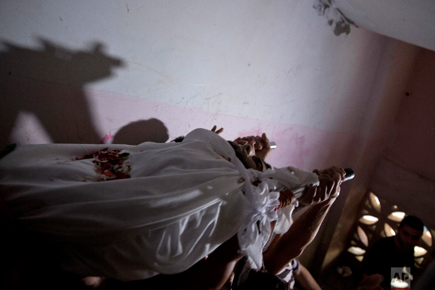 Mourners carry the body of Palestinian Muhammed al-Sadiq, 21, out of the family home during his funeral in Gaza City, Sept. 25, 2018. (AP Photo/Khalil Hamra)