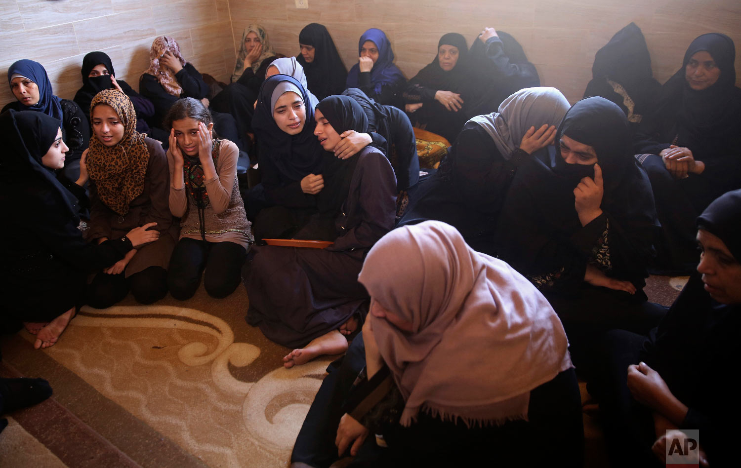 Relatives mourn while waiting for the body of 15-year-old Palestinian Moumin Abu Eiada, during his funeral at his family house in Rafah, southern Gaza Strip, Sept. 20, 2018. (AP Photo/Adel Hana)