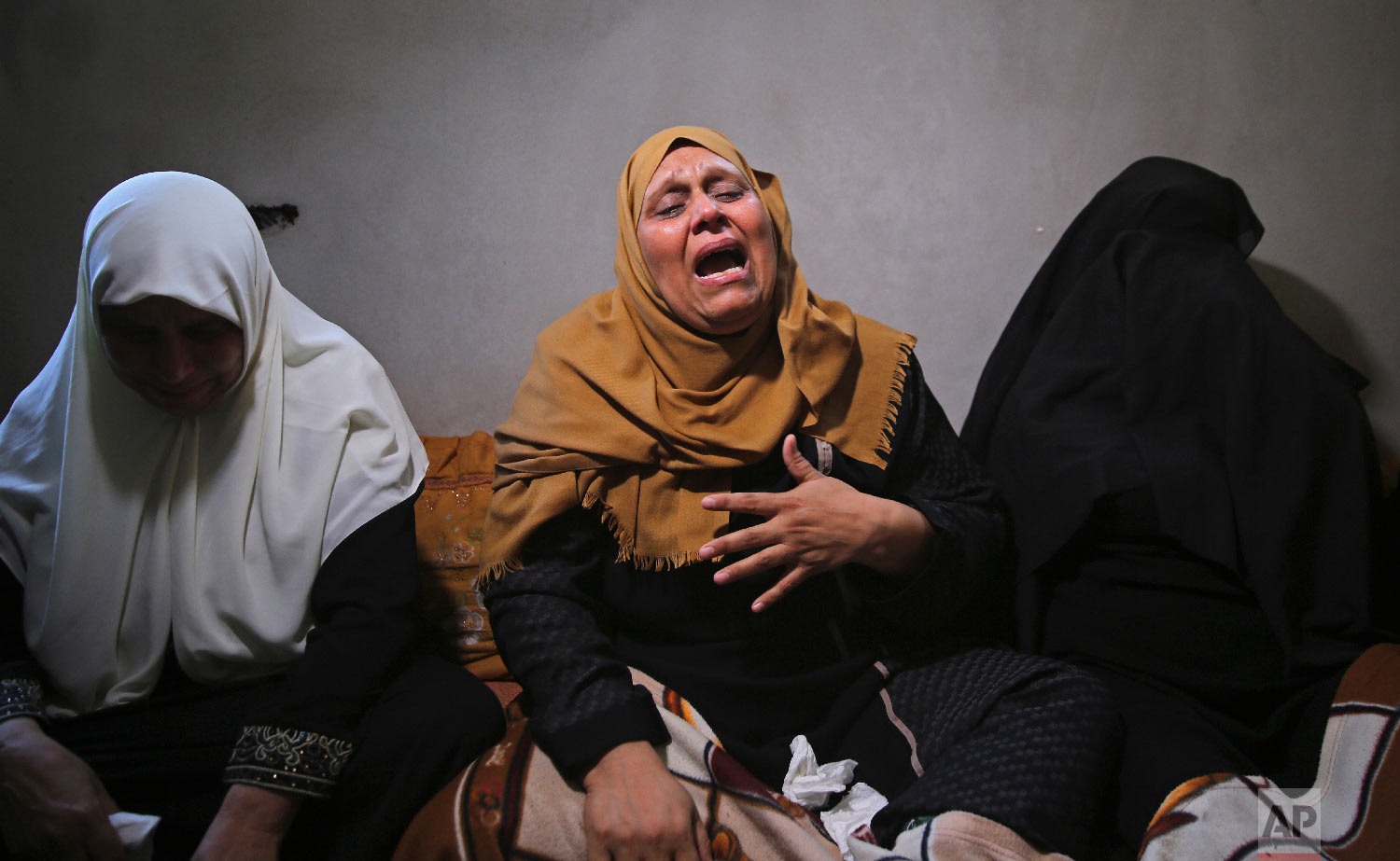 The mother of Ahamd Omar, 20, mourns while waiting with relatives for the body of her son at the family's house during his funeral in the Shati refugee camp, Sept. 19, 2018. (AP Photo/Adel Hana)