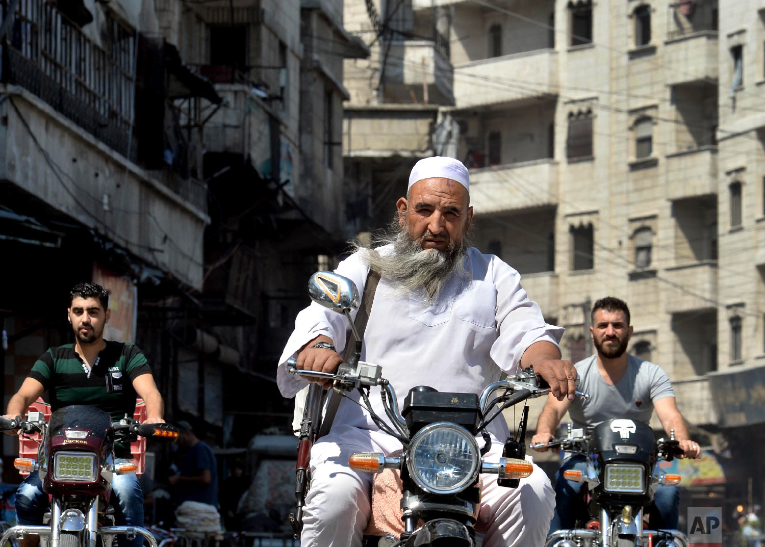 An armed man rides his motorcycle in the center of the northern city of Idlib, Syria on Sept. 10, 2018. (Ugur Can/DHA via AP)