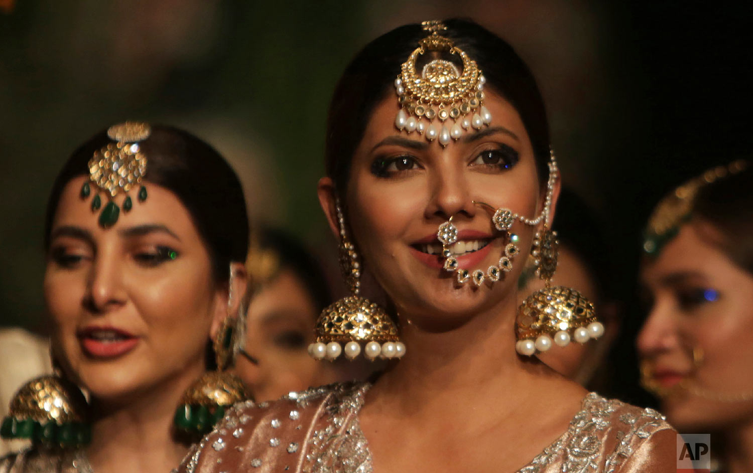 Models present traditional jewelry designed by Nida Azwer during a fashion show by the Loreal Paris Pakistan Fashion Design Council in Lahore, Pakistan, Sept. 5, 2018. (AP Photo/K.M. Chaudary)