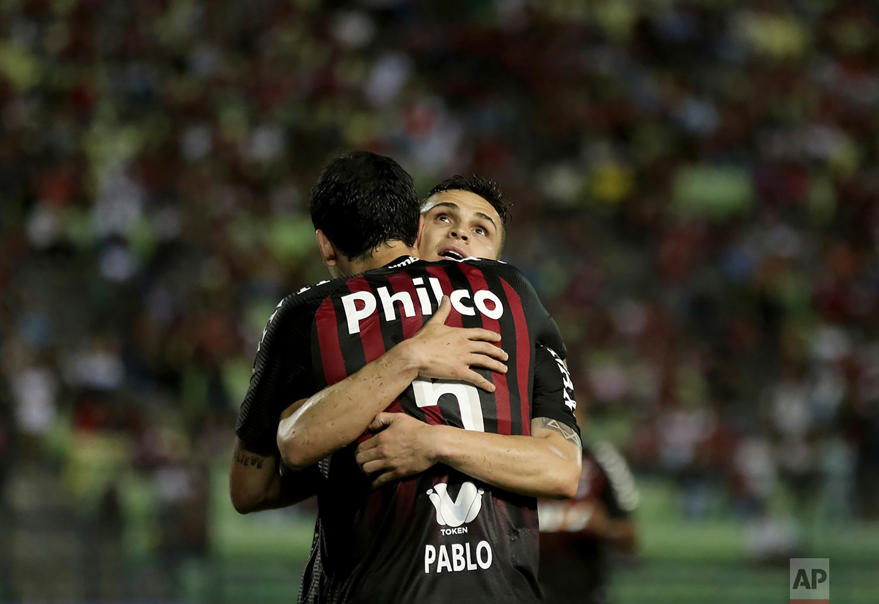 Raphael Veiga of Brazil's Atletico Paranaense celebrates with his teammate Pablo, after scoring his second goal against Venezuela's Caracas FC during their Copa Sudamericana soccer match in Caracas, Venezuela, Sept. 19, 2018.(AP Photo/Fernando Llano)