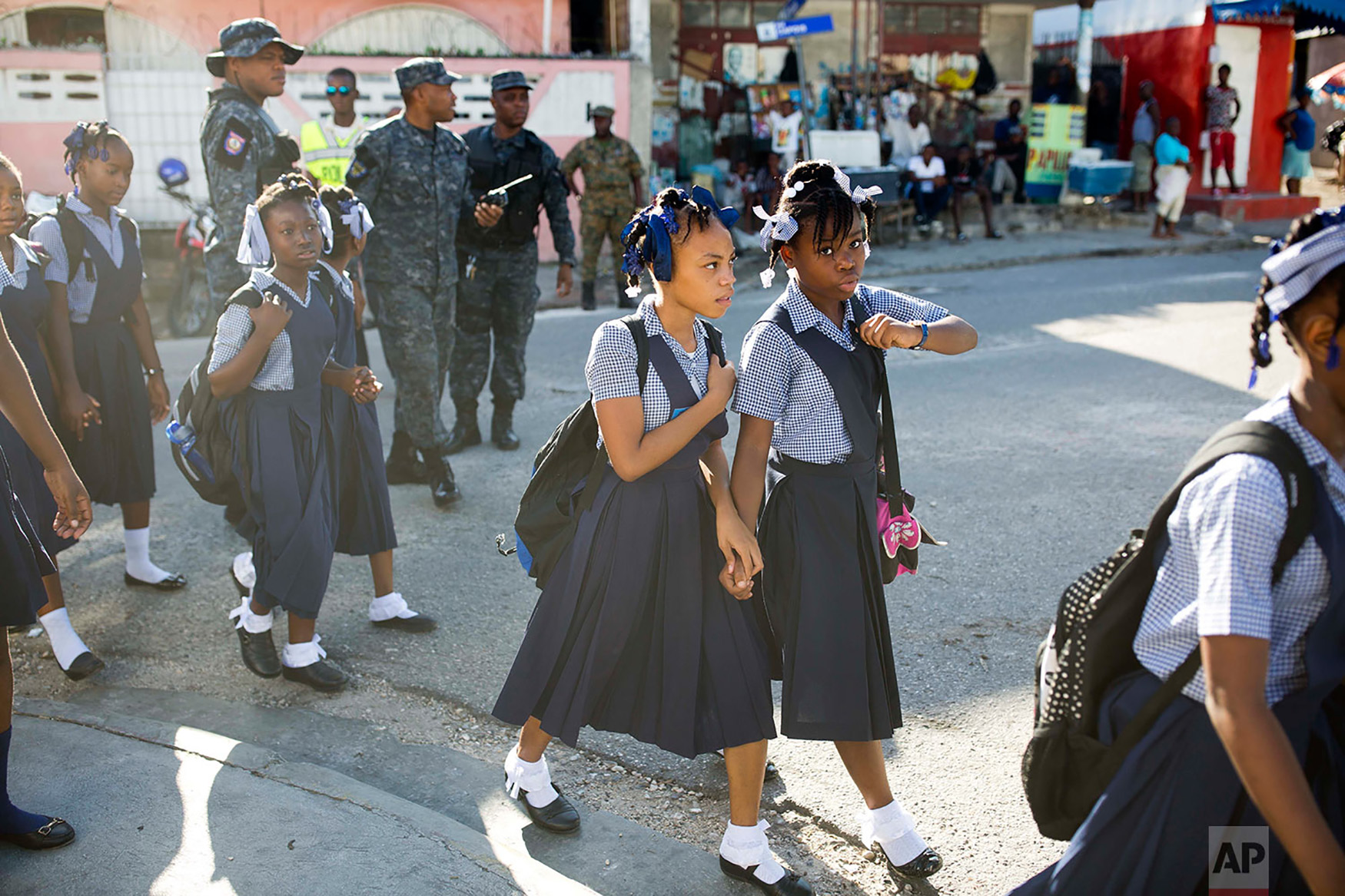 Students arrive hand in hand to the Brazilian National School before the start of a ceremony marking the first day back to class in Port-au-Prince, Haiti, Sept. 3, 2018. (AP Photo/Dieu Nalio Chery)