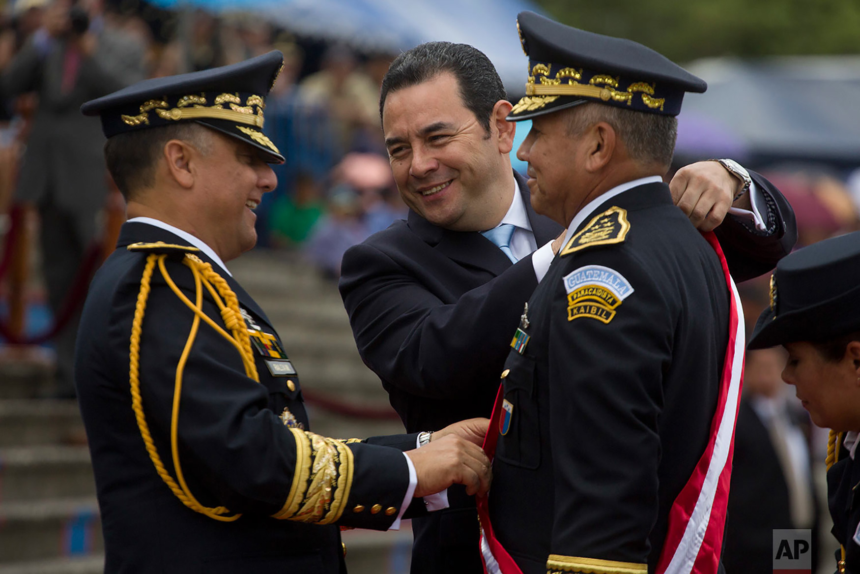 Guatemalan President Jimmy Morales center, places a sash on general Manuel Pineda Saravia, right, during the 145th anniversary of the Military school in San Juan Sacatepequez, Guatemala, Sept. 1, 2018. Morales announced Friday that he is shutting down a crusading U.N.-sponsored anti-graft commission that pressed a number of high-profile corruption probes, including one pending against the president himself over purported illicit campaign financing. (AP Photo/Moises Castillo)