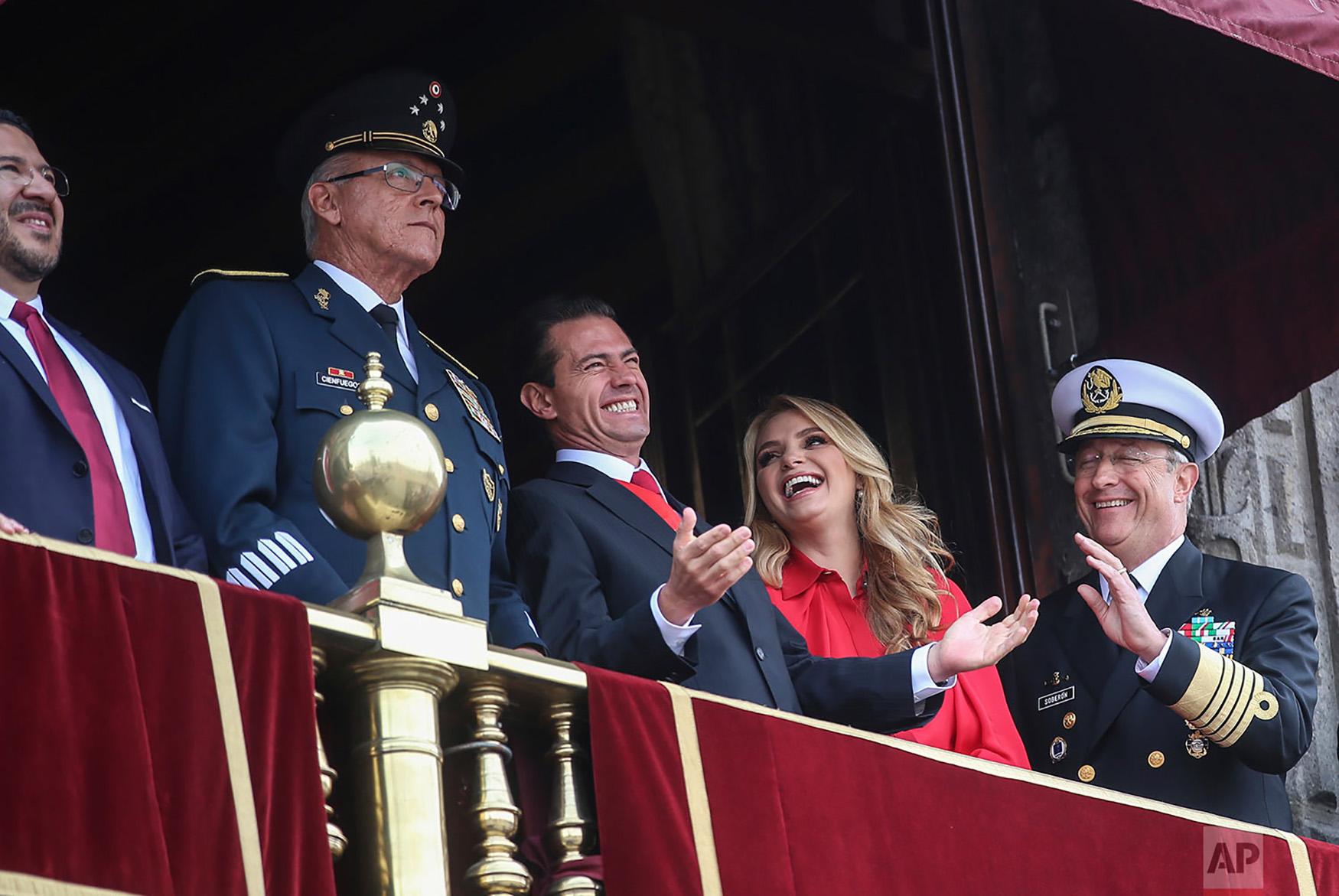Mexican President Enrique Pena Nieto, center left, and first lady Angelica Rivera, share a laugh with Admiral Vidal Soberon, right, during the Independence Day military parade in the Zocalo of Mexico City, Sept. 16, 2018. Mexico is celebrating its independence from Spain. (AP Photo/Anthony Vazquez)