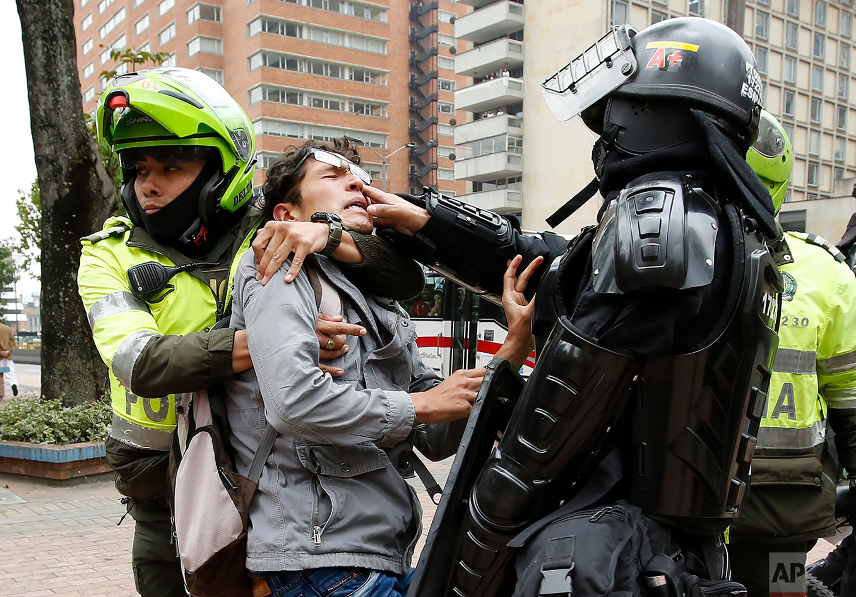 Police detain a man who was blocking traffic during a protest against a decree by Colombia's President Ivan Duque that would allow police to confiscate any amount of drugs from people in the street in Bogota, Colombia, Sept. 6, 2018. In 2012, Colombia's Constitutional Court approved a government bill to decriminalize the possession of small quantities of drugs for personal use. (AP Photo/Fernando Vergara)