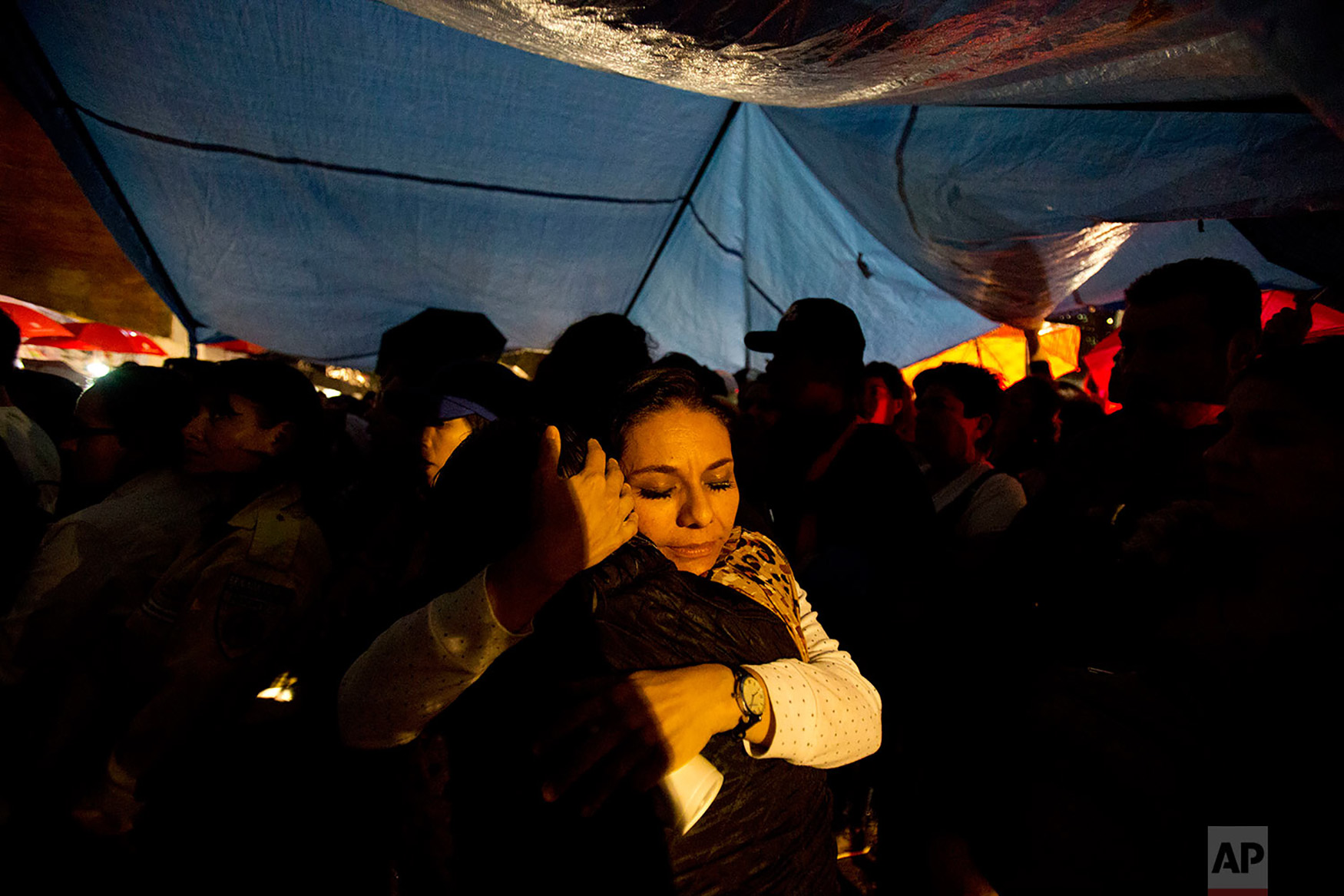 Victims' family members hug during an evening memorial ceremony at Alvaro Obregon 286, where 49 died when their office building collapsed in last year's 7.1 magnitude earthquake, in Mexico City, Sept. 19, 2018. Across the city, memorials were held at sites where hundreds perished in the quake one year ago. (AP Photo/Rebecca Blackwell)