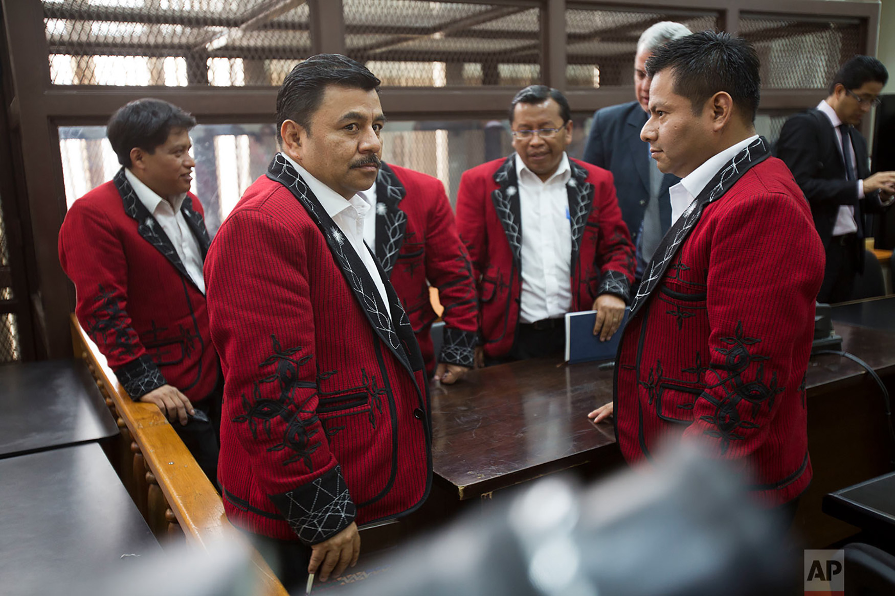 Lawyer Edgar Perez Archila, second from left, and his coworkers, representing the Ixil population and wearing traditional jackets, stand in the courtroom during the last hearing of the former director of military intelligence, Jose Rodriguez Sanchez in Guatemala City, Sept. 26, 2018. Rodriguez Sanchez awaits a new sentence for the crime of genocide, for which he was previously tried along with the late former dictator Efrain Rios Montt in 2013. (AP Photo/Moises Castillo)
