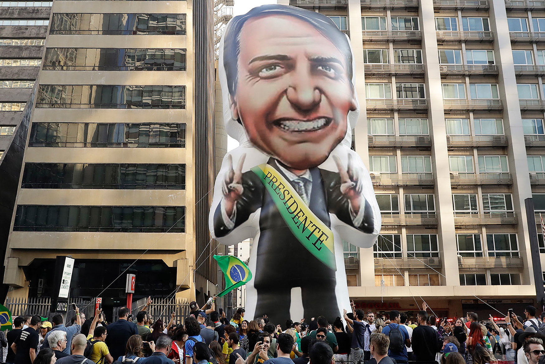 Supporters of Jair Bolsonaro, presidential candidate for the National Social Liberal Party who was stabbed during a campaign event days ago, exhibit a large, inflatable doll in his image as they march along Paulista Avenue to show support for him in Sao Paulo, Brazil, Sept. 9, 2018. (AP Photo/Andre Penner)