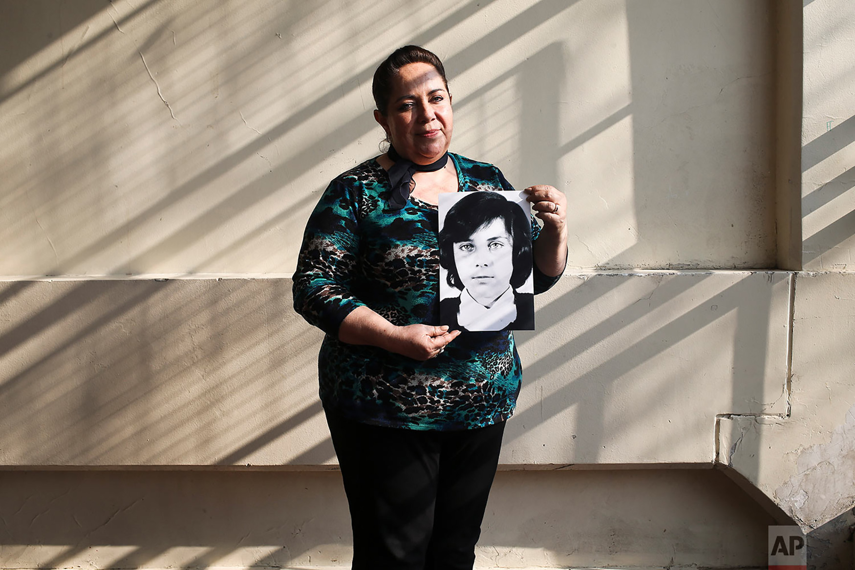 "Vittoria E Natto poses for a portrait inside her high school holding a photo of herself when she was 9 years old, in Santiago, Chile, Sept. 6, 2018. Soon after the Sept. 11, 1973 coup, on her 9th birthday, two armed marines entered and pointed guns at Vittoria. She watched her father hand her mother over to them. Vittoria began to shout and kick, angering the officer overseeing the arrest. ""Take her!"" he shouted to to her father. And so he did, Vittoria now recalls, raping his own child on the spot. (AP Photo/Esteban Felix)"