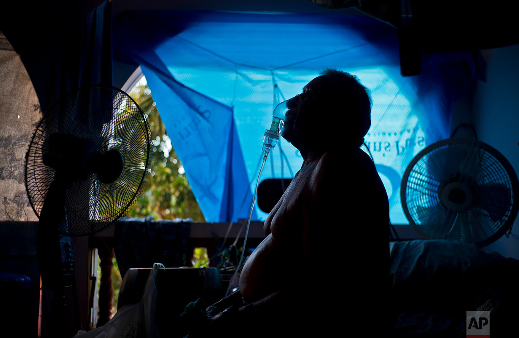 Gilberto Cosme Rodriguez takes one of his 10 a day asthma treatments to help him breathe, inside his home still covered with a tarp after FEMA assistance failed to cover the cost of fixing his roof that was torn off by last year's Hurricane Maria in Naranjito, Puerto Rico, Sept. 9, 2018. Rodriguez, who has one working lung due to pulmonary fibrosis triggered by the use of chemicals when he worked in construction, said every morning he needs treatment to get out of bed. (AP Photo/Ramon Espinosa)