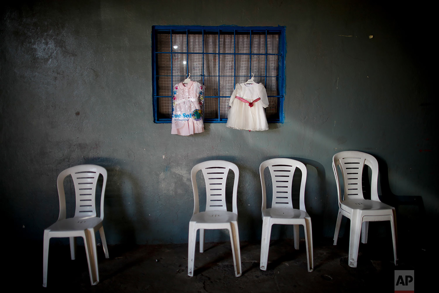 Dresses hang for exchange at a barters market set up by residents inside a community center on the outskirts of Buenos Aires, Argentina, Sept. 6, 2018. Despite several interest rate hikes by the Argentine Central Bank, the peso has lost more than half its value in less than a year. (AP Photo/Natacha Pisarenko)