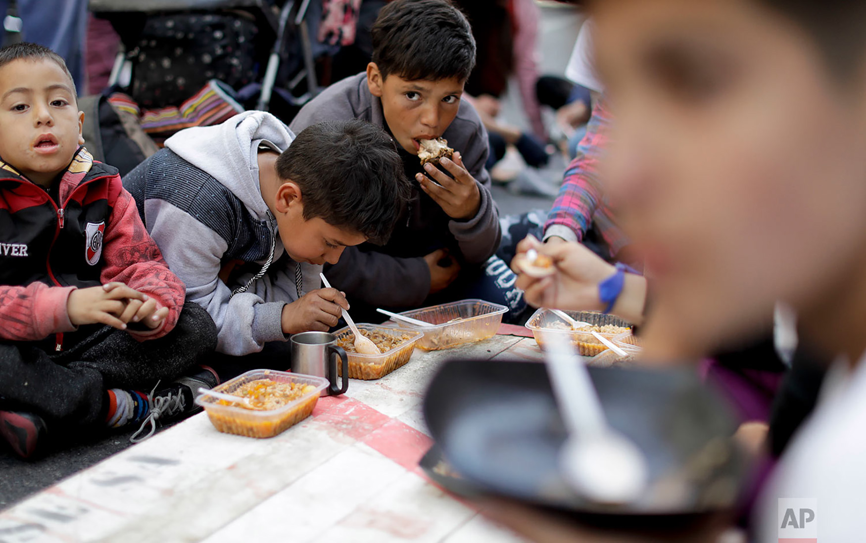 Children eat free food where demonstrators set up a soup kitchen along a main avenue that connects the government house with Congress as a way to protest government economic measures in Buenos Aires, Argentina, Sept. 11, 2018. Consumer prices are soaring, unemployment is high and the Argentine peso has plunged, bringing back haunting memories of the country's economic meltdown in 2001 that pushed millions into poverty. (AP Photo/Natacha Pisarenko)