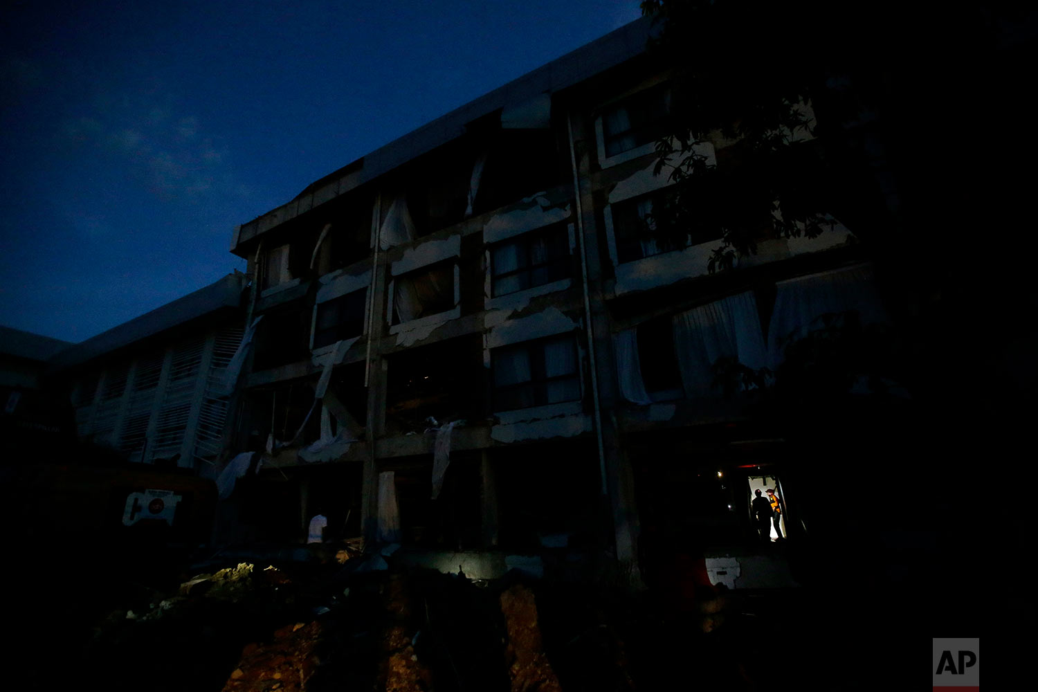 French rescuers join their Filipino counterparts as they check for survivors as night falls at the heavily damaged Mercure hotel after a massive earthquake and tsunami hit Palu, Central Sulawesi, Indonesia, Oct. 4, 2018. (AP Photo/Aaron Favila)