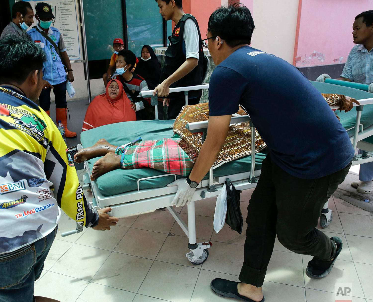 An injured man is brought to the hospital as one woman cries after learning about her daughter's death in a massive earthquake and tsunami in Palu, Central Sulawesi, Indonesia, Oct. 4, 2018. (AP Photo/Aaron Favila)